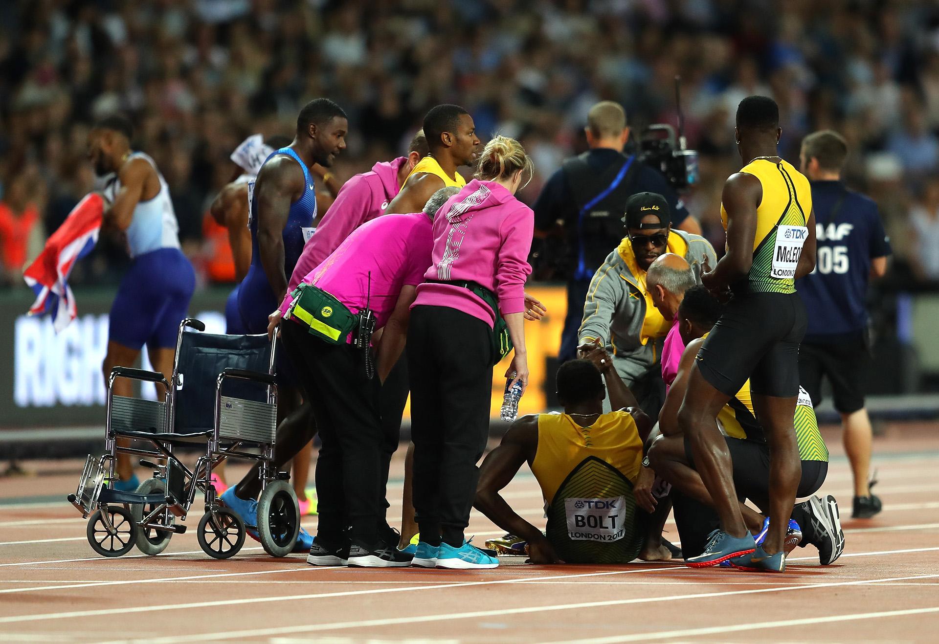 Ayudan a levantarse a Bolt; en el fondo, celebra Gran Bretaña