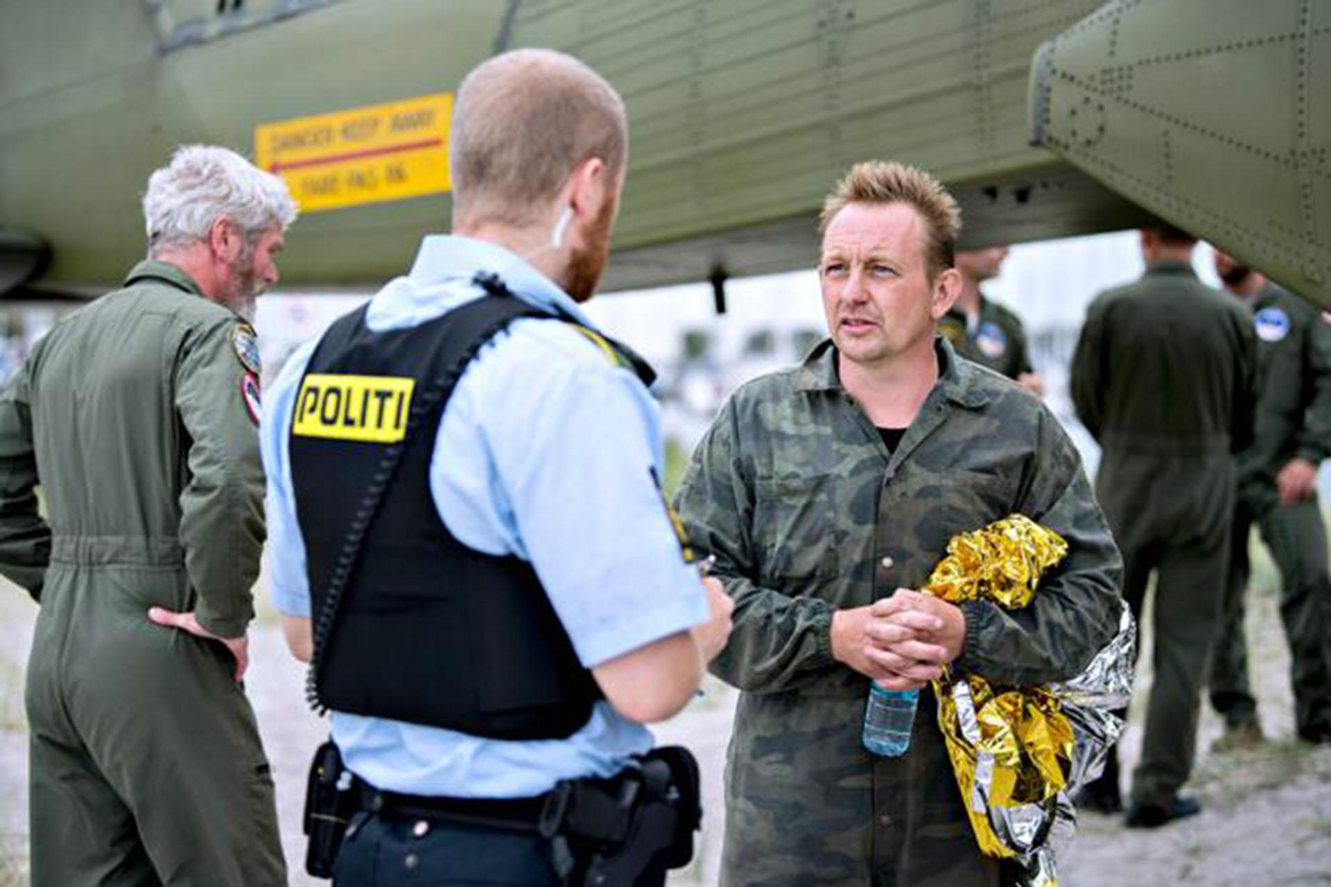 El sospechoso, Peter Madsen, con la policía junto al submarino (Bax Lindhardt / AFP)