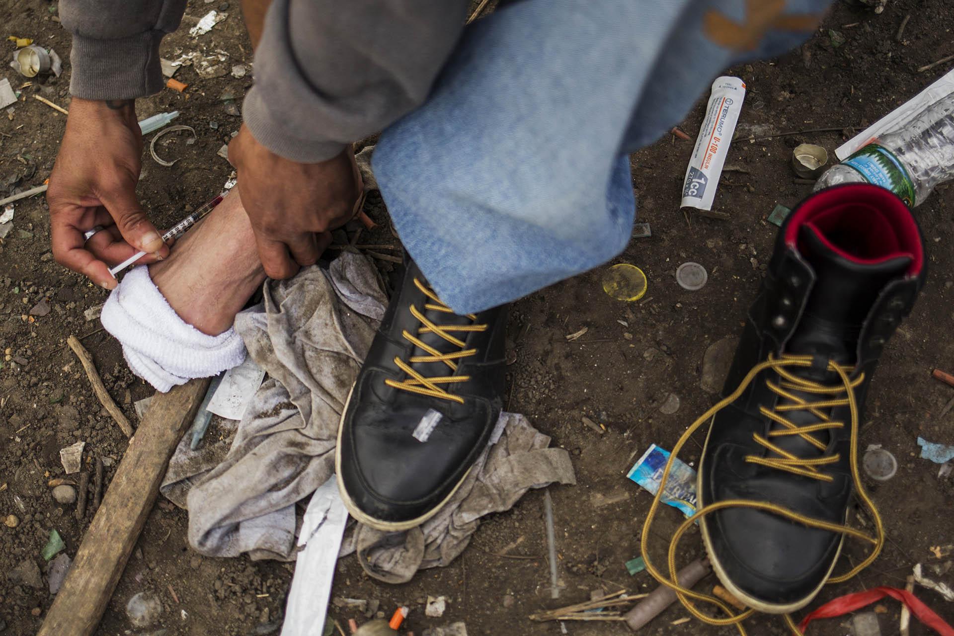 Un hombre se inyecta heroína en el pie (AFP)