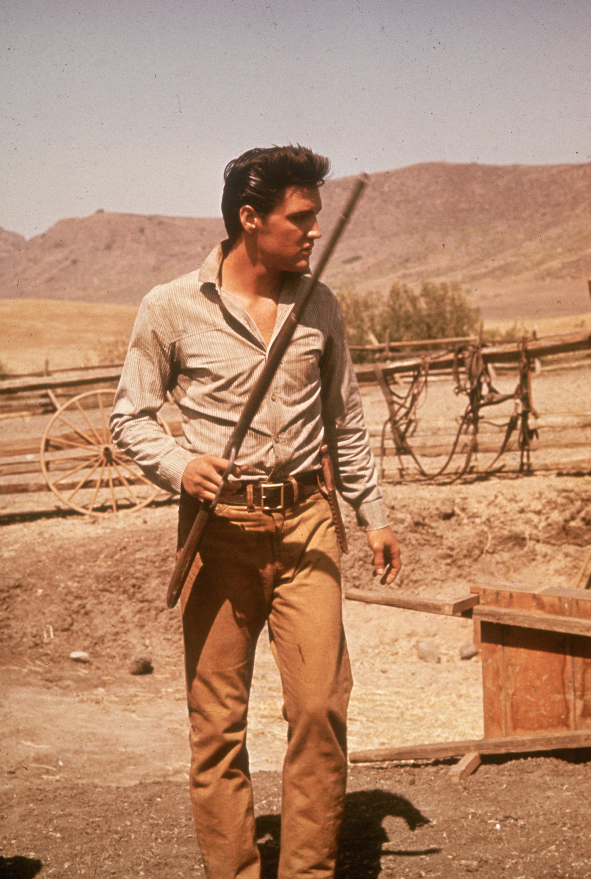 Além de ser um músico brilhante, ele se destacou em atuar.  No set de filmagem completo, Elvis com uma espingarda na mão.  Gabardine camel pants com cinto e camisa com decote em V (Foto de Hulton Archive / Getty Images)