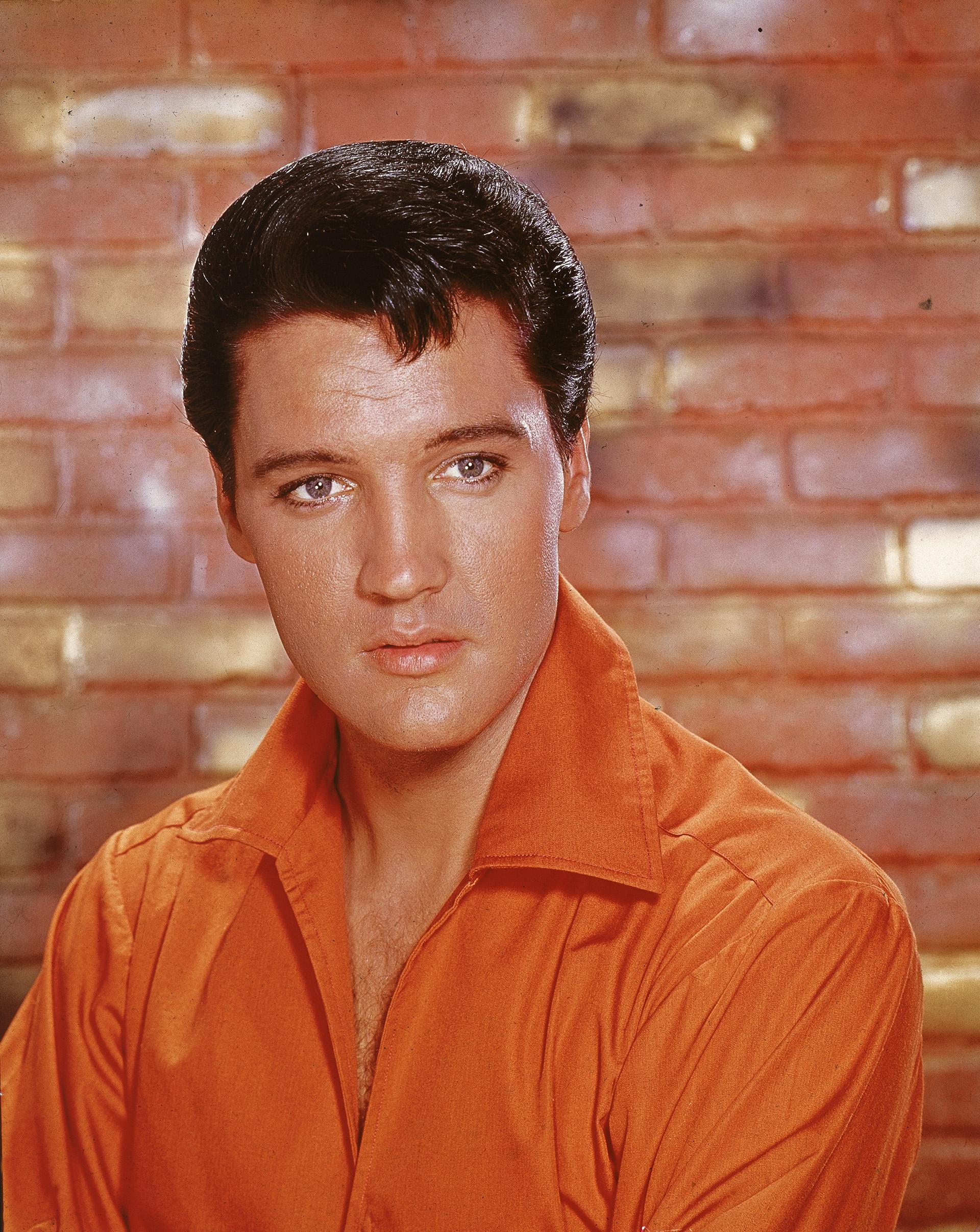 Um retrato do rei do Rock and Roll com sua aparência sedutora e uma impressionante camiseta laranja com gola em V e lapela larga no pescoço, uma tendência dos anos 60 (Foto de Hulton Archive / Getty Images)