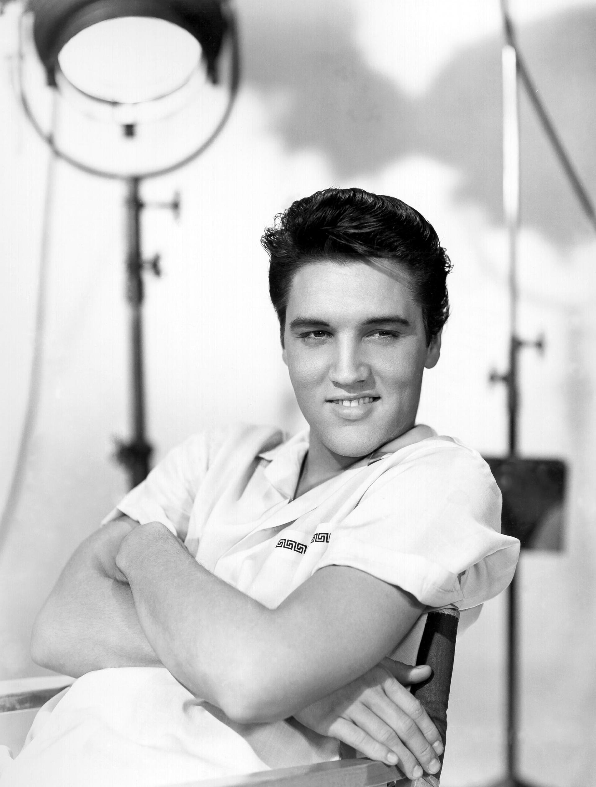 Em sua cadeira de cinema e com refletores de luz de fundo, Elvis participou de 36 filmes, incluindo documentários sobre sua vida pessoal e carreira.