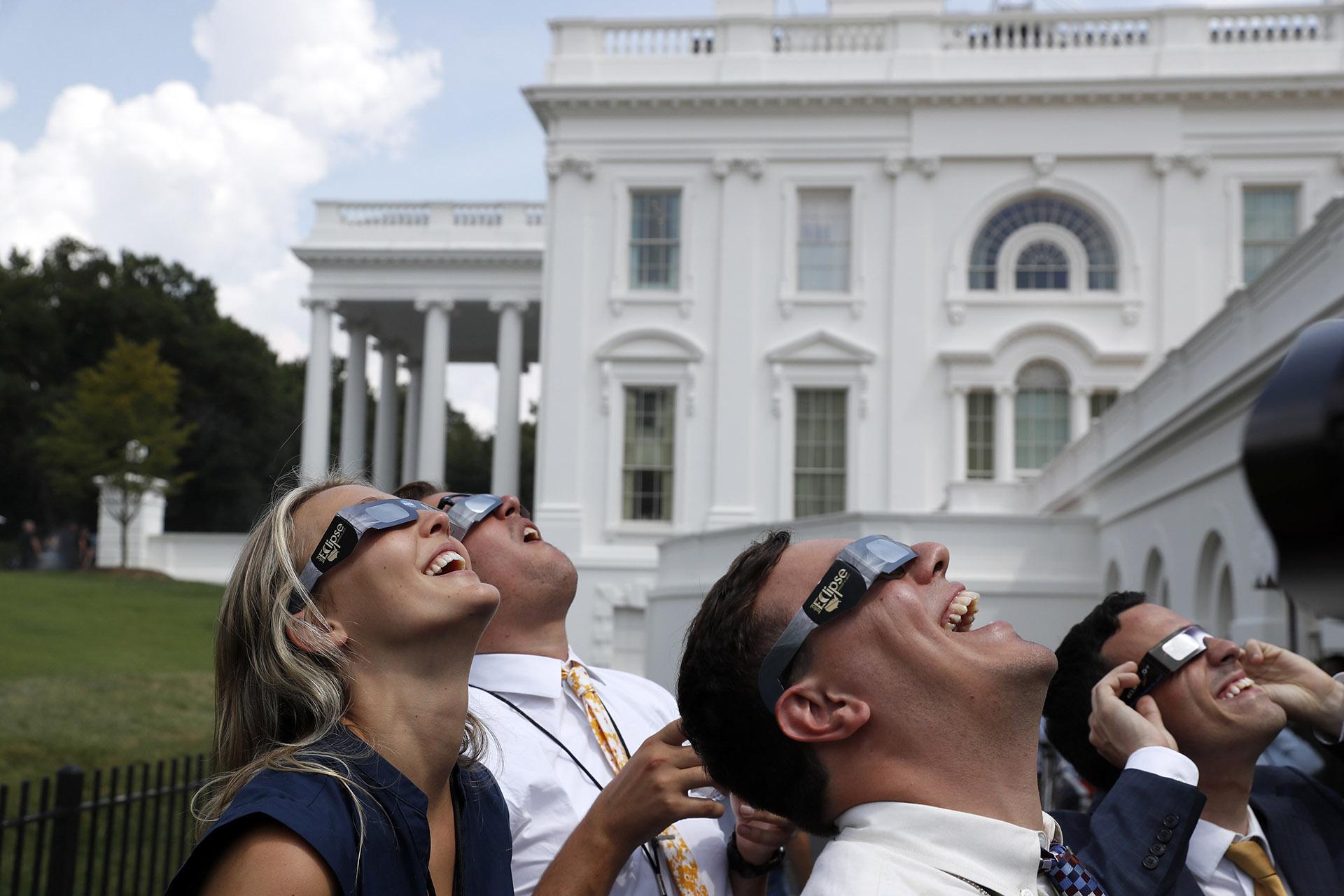 El personal de la Casa Blanca sonríe mientras observan el eclipse con gafas solares