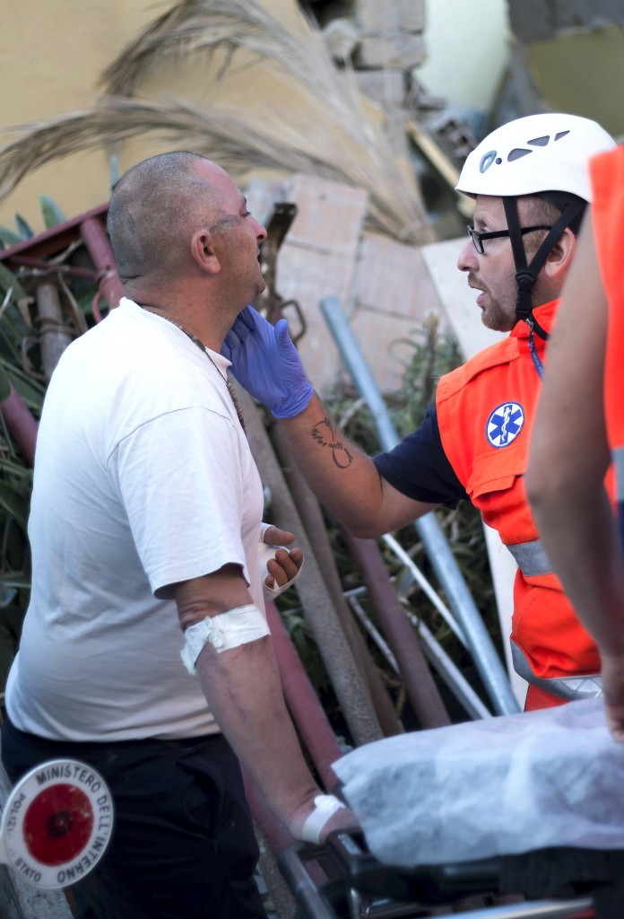 The father of two children stuck in the rubble talks with an emergency worker in front of his collapsed house in Ischia, on August 22, 2017, after an earthquake hit the popular Italian tourist island off the coast of Naples, causing several buildings to collapse overnight. A magnitude-4.0 earthquake struck the Italian holiday island of Ischia, causing destruction that left two people dead at peak tourist season, authorities said, as rescue workers struggled early to free two children from the rubble. / AFP PHOTO / Eliano IMPERATO /