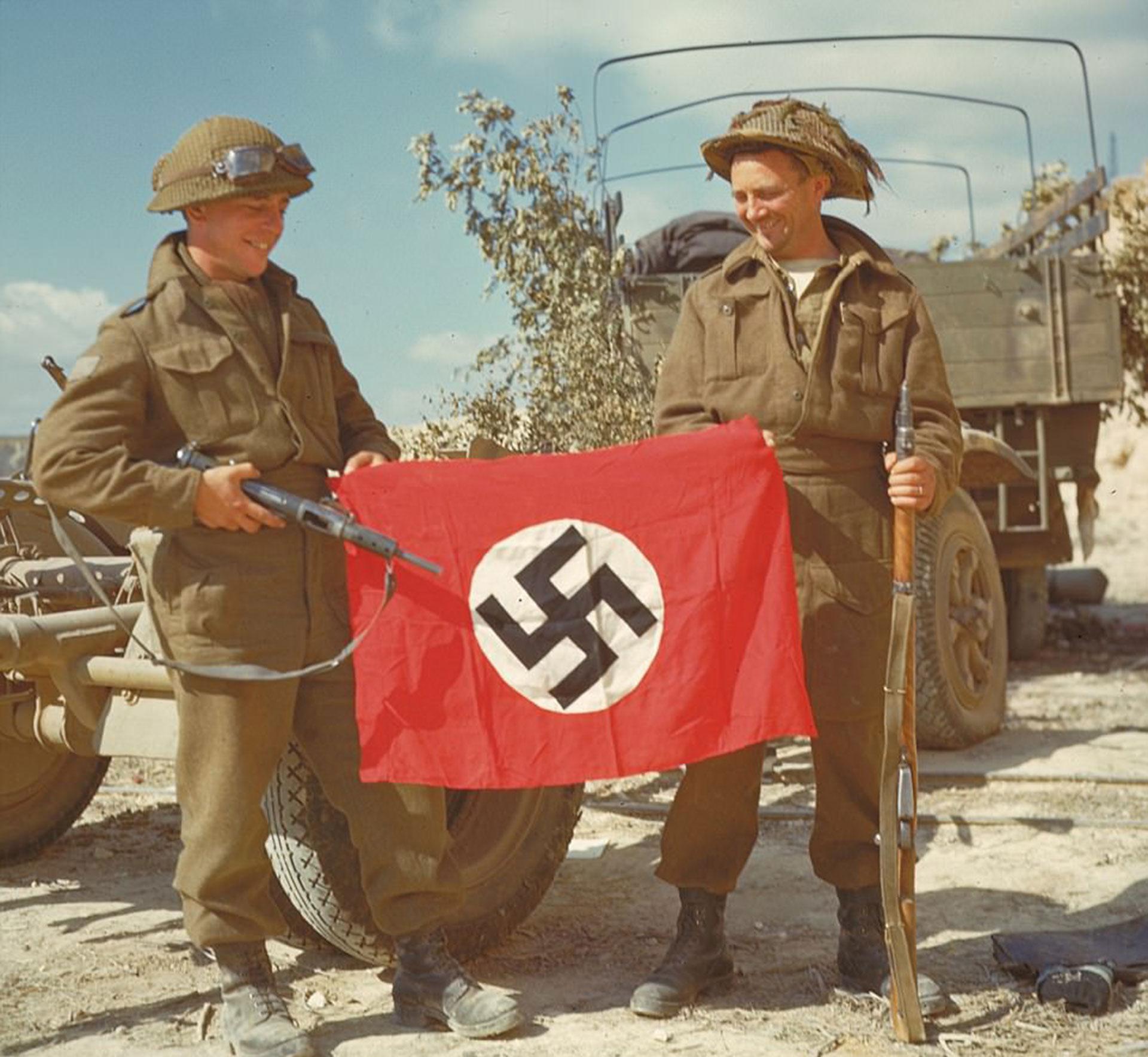 Dos soldados canadienses sostienen una bandera nazi capturada luego del desembarco en Normandía (National Archives of Canada)