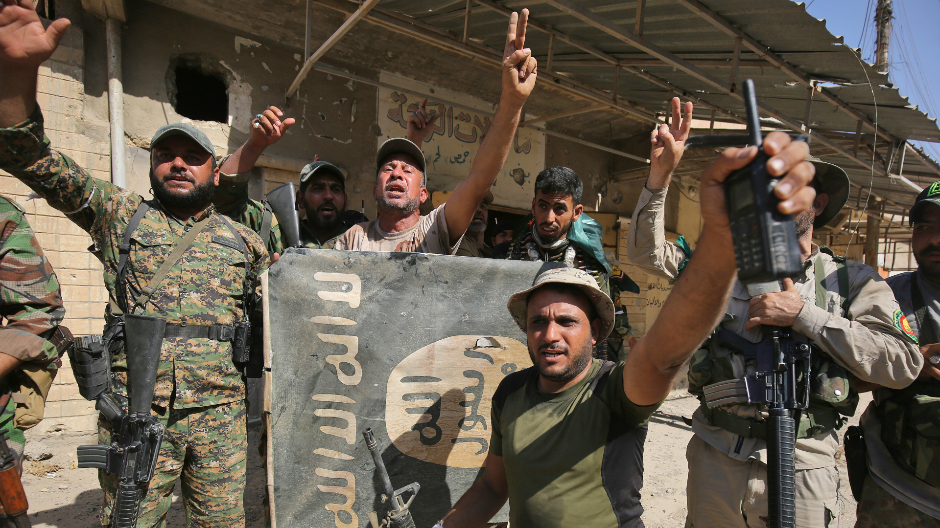 Milicianos de Hashd al Shaabi sostienen una bandera del ISIS mienstras celebran la conquista de otro barrio (AFP)