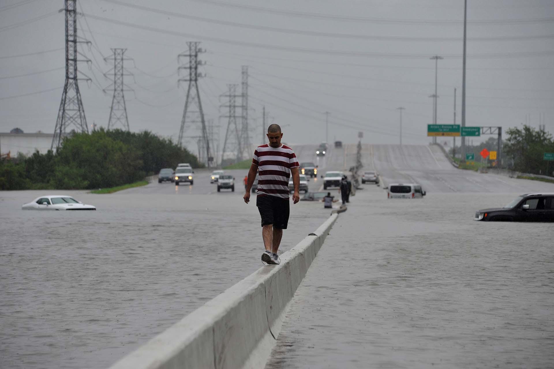 Un hombre trata de escapar de las inundaciones en Houston (REUTERS)