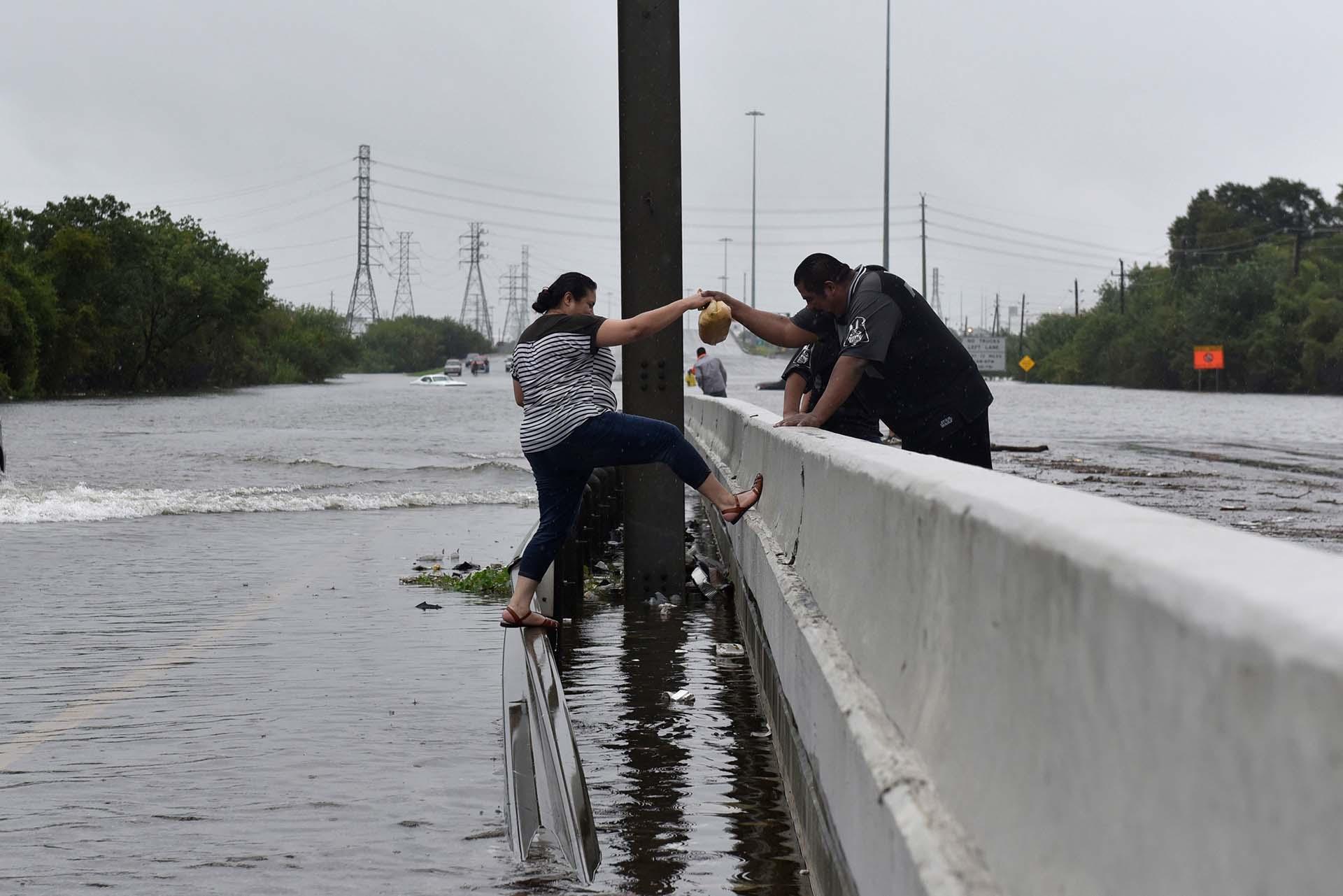Un policía ayuda a una mujer a evitar caer al agua (REUTERS)