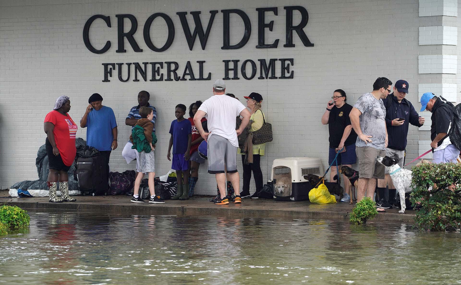 Un grupo de personas espera la ayuda de las autoridades locales (REUTERS)