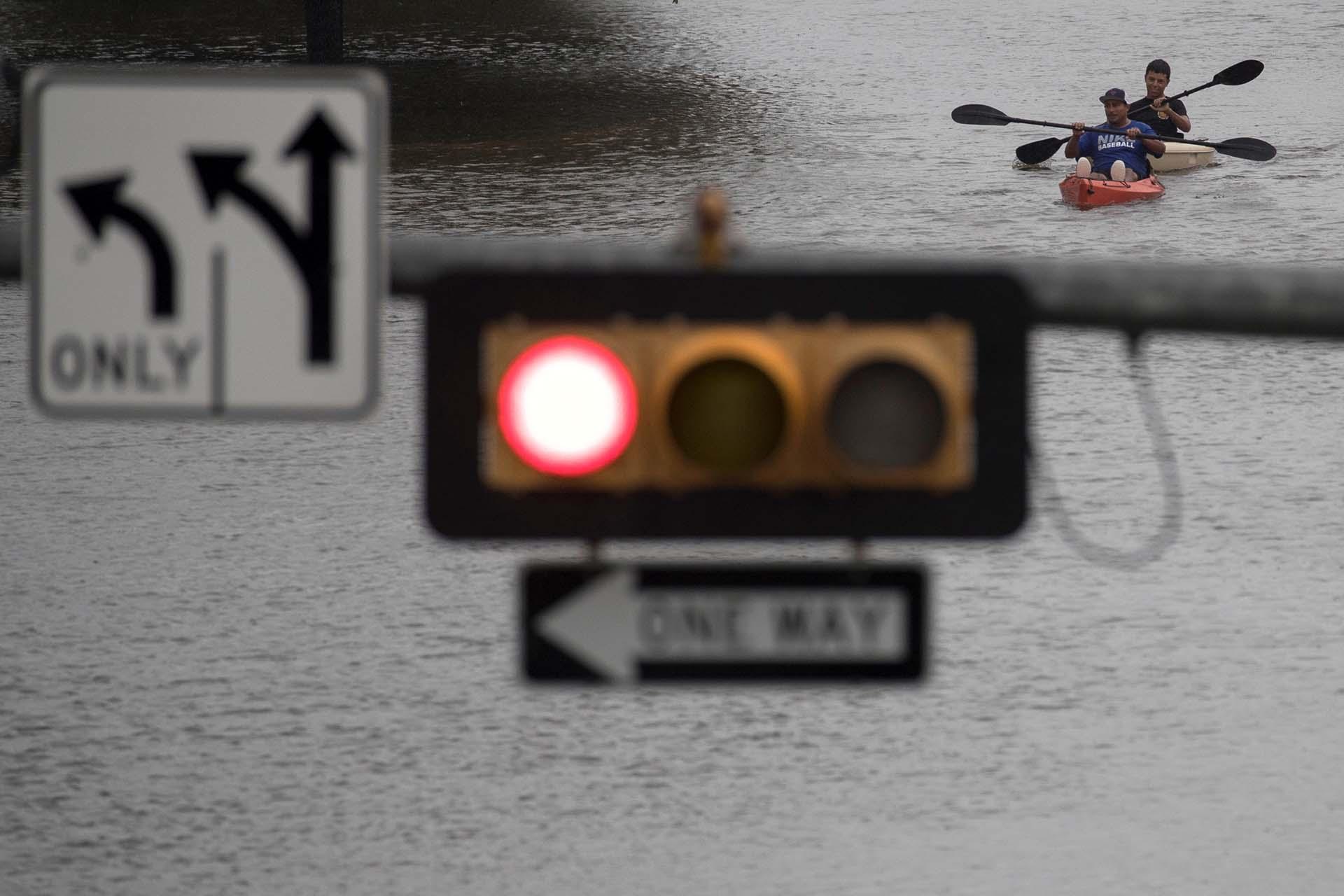 Dos hombres transitan una calle en kayak(REUTERS)