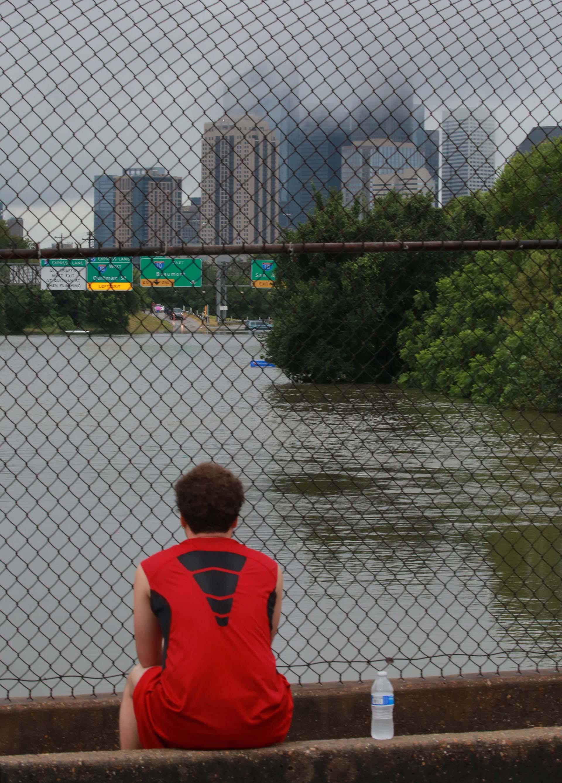 Un corredor observa cómo el agua fluye por las calles (REUTERS)