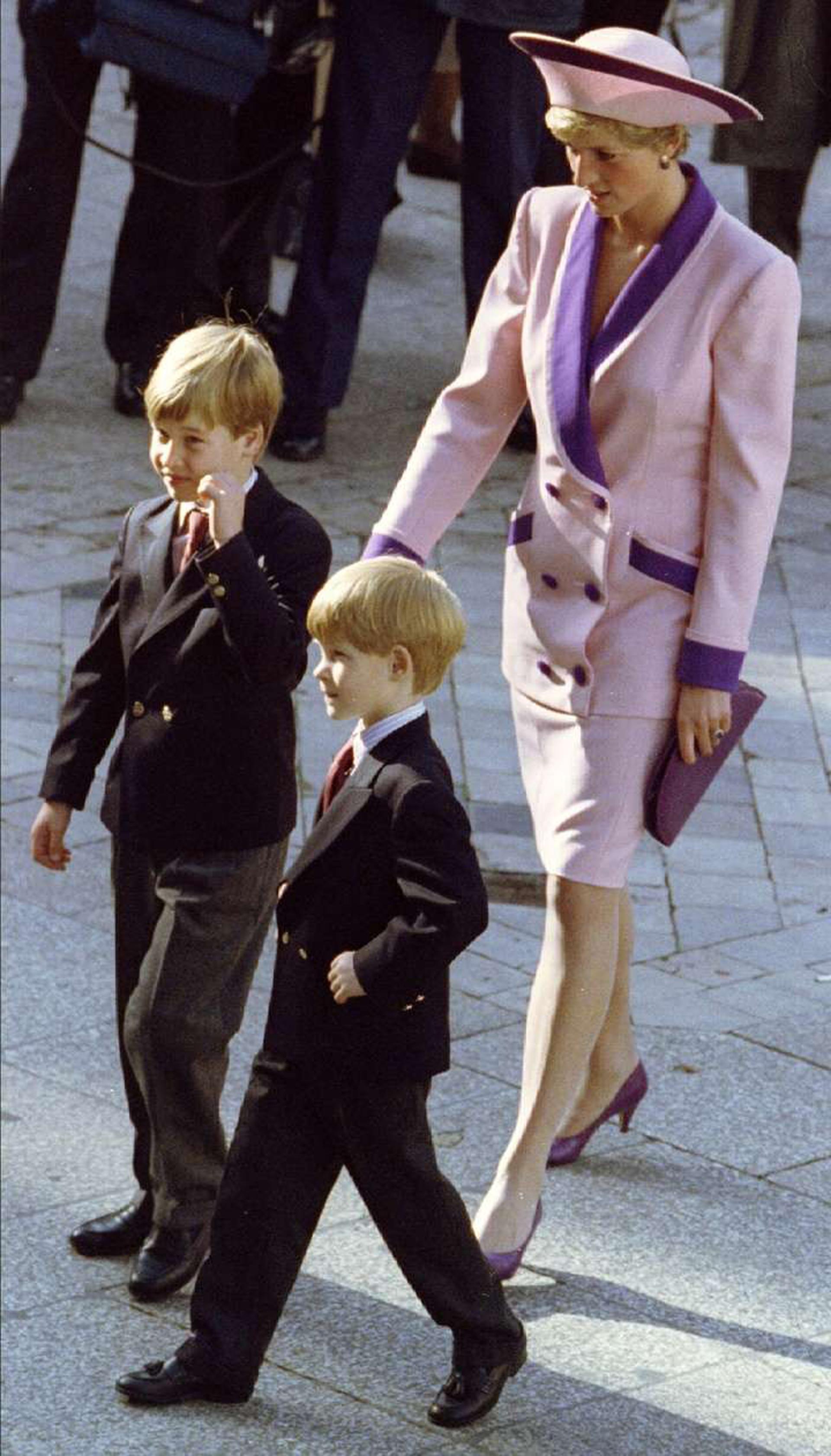 Diana en compañía de sus dos hijos, ambos luciendo trajes con camisa y corbata. Ellacon tallieur en falda y bicolor en rosa pastel y violeta