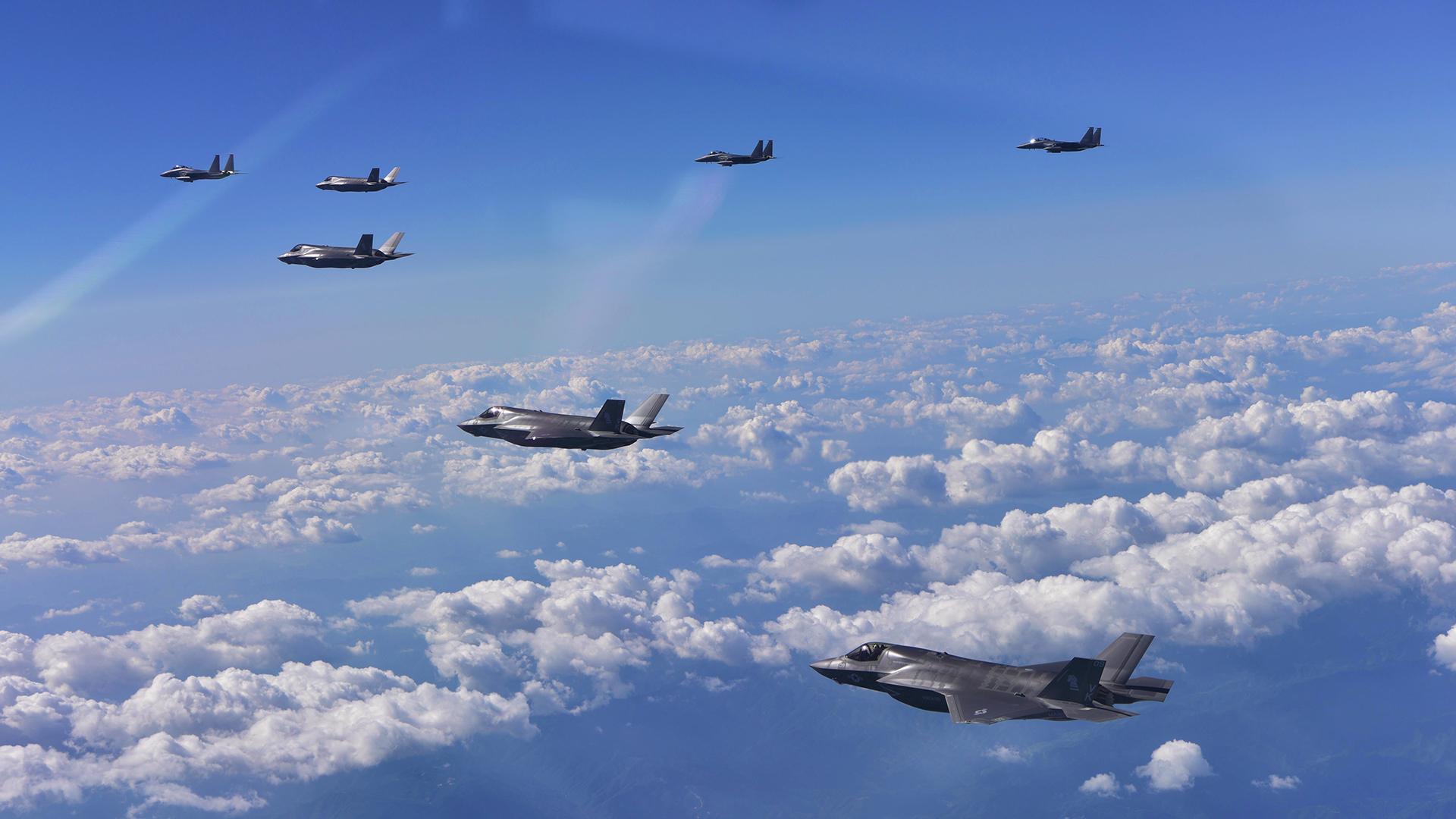 Tres cazas F-15K surcoreanos, en el fondo, y cuatro F-35B furtivos de la fuerza aérea de Estados Unidos (AFP)