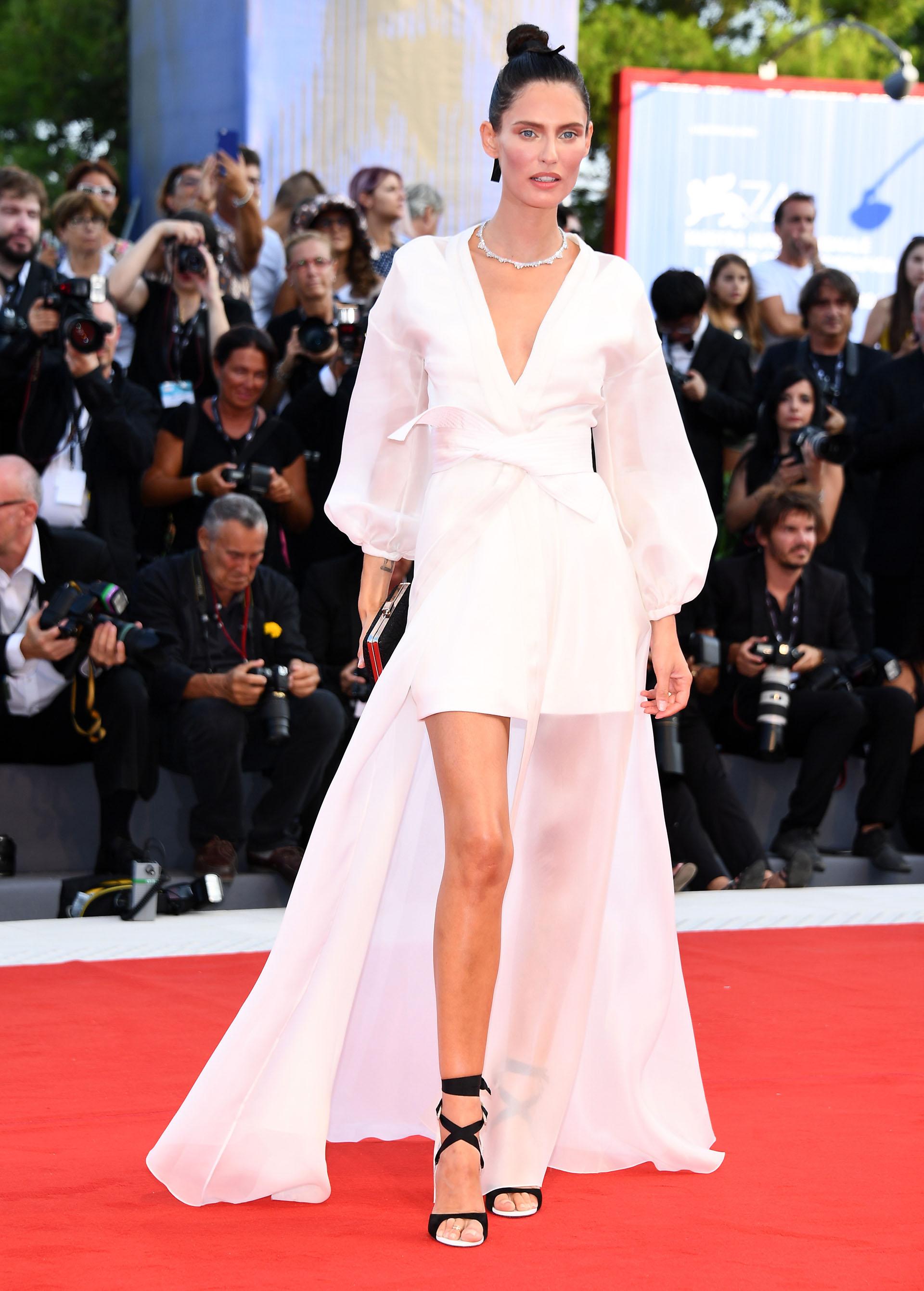 El total white look de Bianca Balti levantó las miradas de los invitados. Escogió una pieza asimétrica de OVS que completó con un peinado de aires orientales (Pascal Le Segretain/Getty Images)