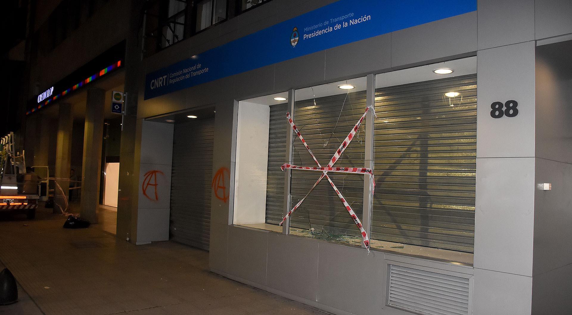 Vidrios rotos y pintadas en el edificio de la CNRT (Comisión Nacional de Regulación del Transporte) y el Banco Credicoop, en Maipú entre el 62 y 88