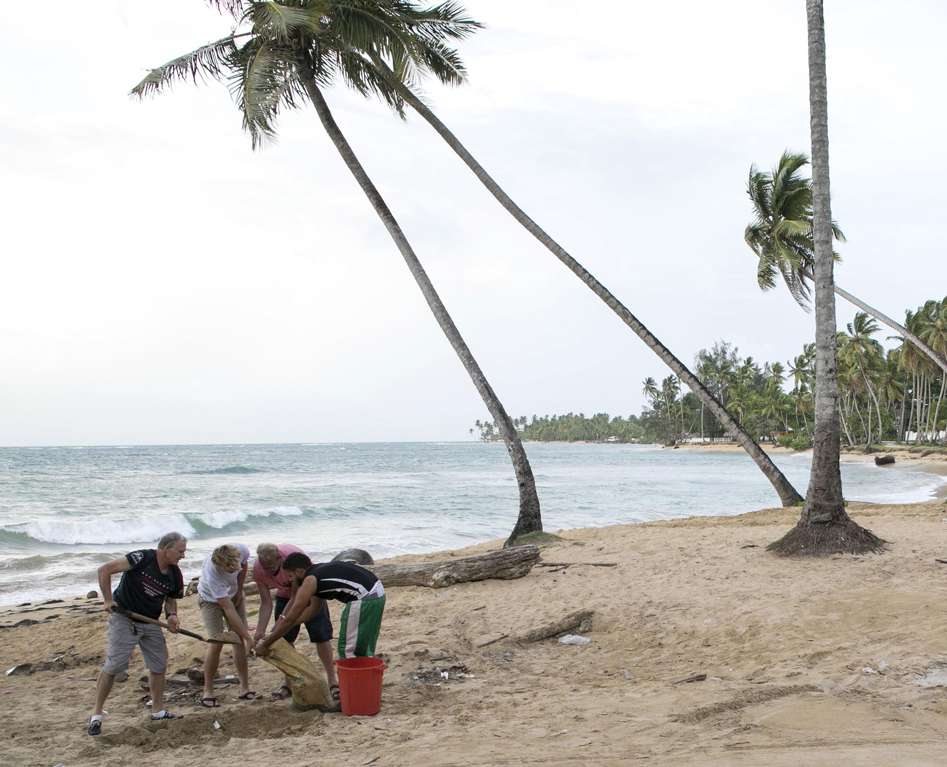 Un grupo de personas juntan arena para proteger sus casas del huracán en República Dominicana (AP Photo)