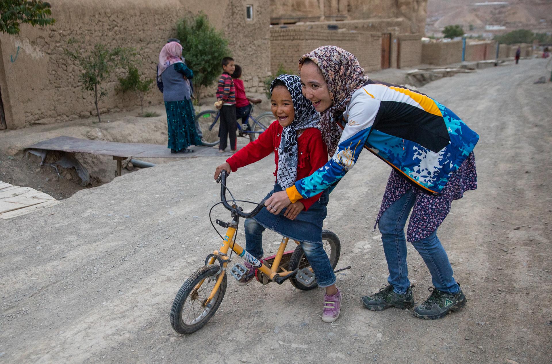 Zakia Mohammadhi, de 23 años de edad, empuja a su hermana menor, Honey, de 7 años de edad en bicicleta hasta su casa, que se encuentra en un camino de tierra hasta una colina que puede ser todo un reto para un niño. (Paula Bronstein)