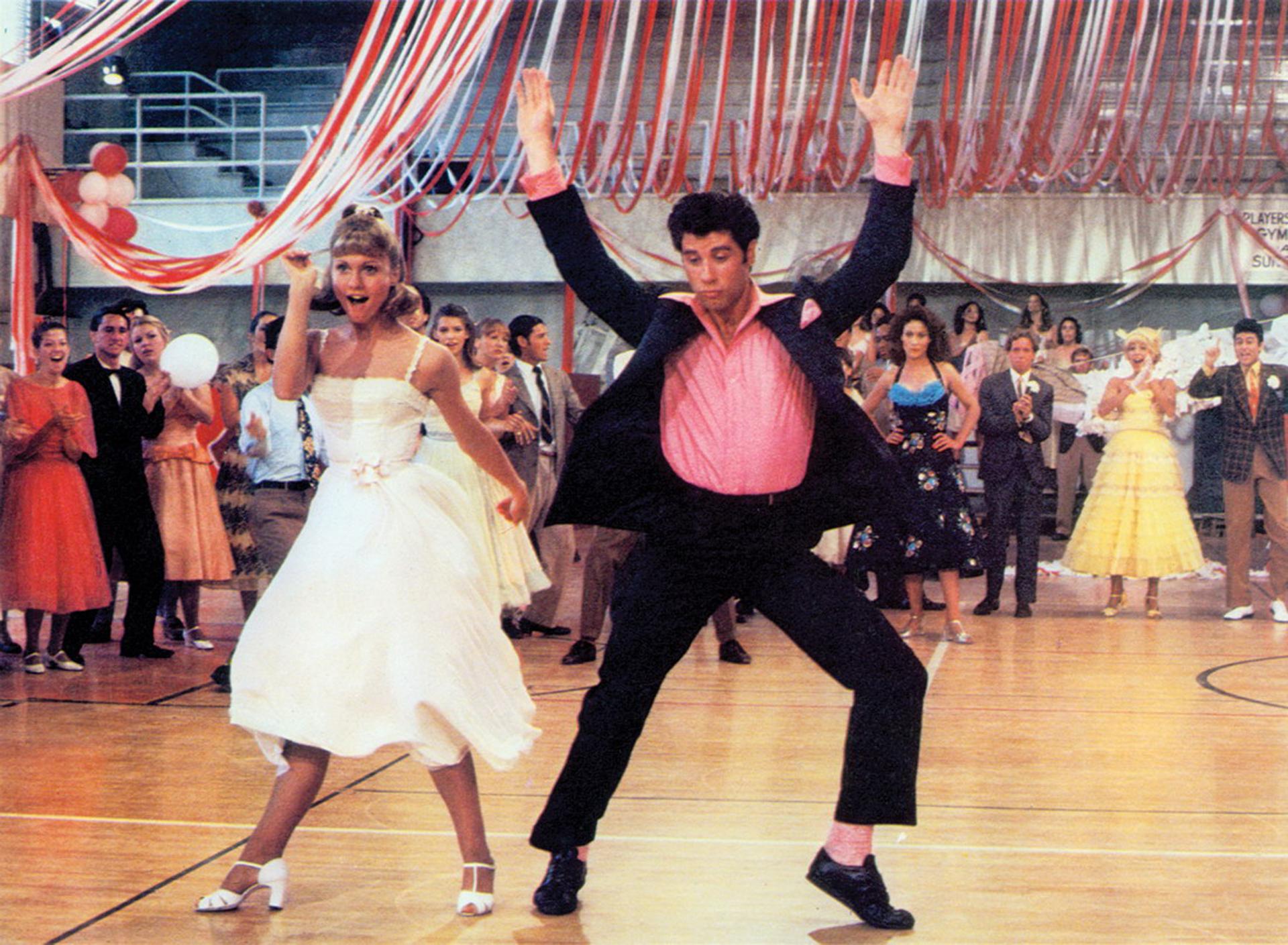 Olivia Newton en la piel de Sandy Olsson para 'Grease' en la escena donde bailan, ella luce un vestido blanco con corte en la cintura de seda. Los zapatos de bailarina con boca de pez acompañaron su vestuario. John, por su parte, en rosa y negro con un impecable traje y zapatos