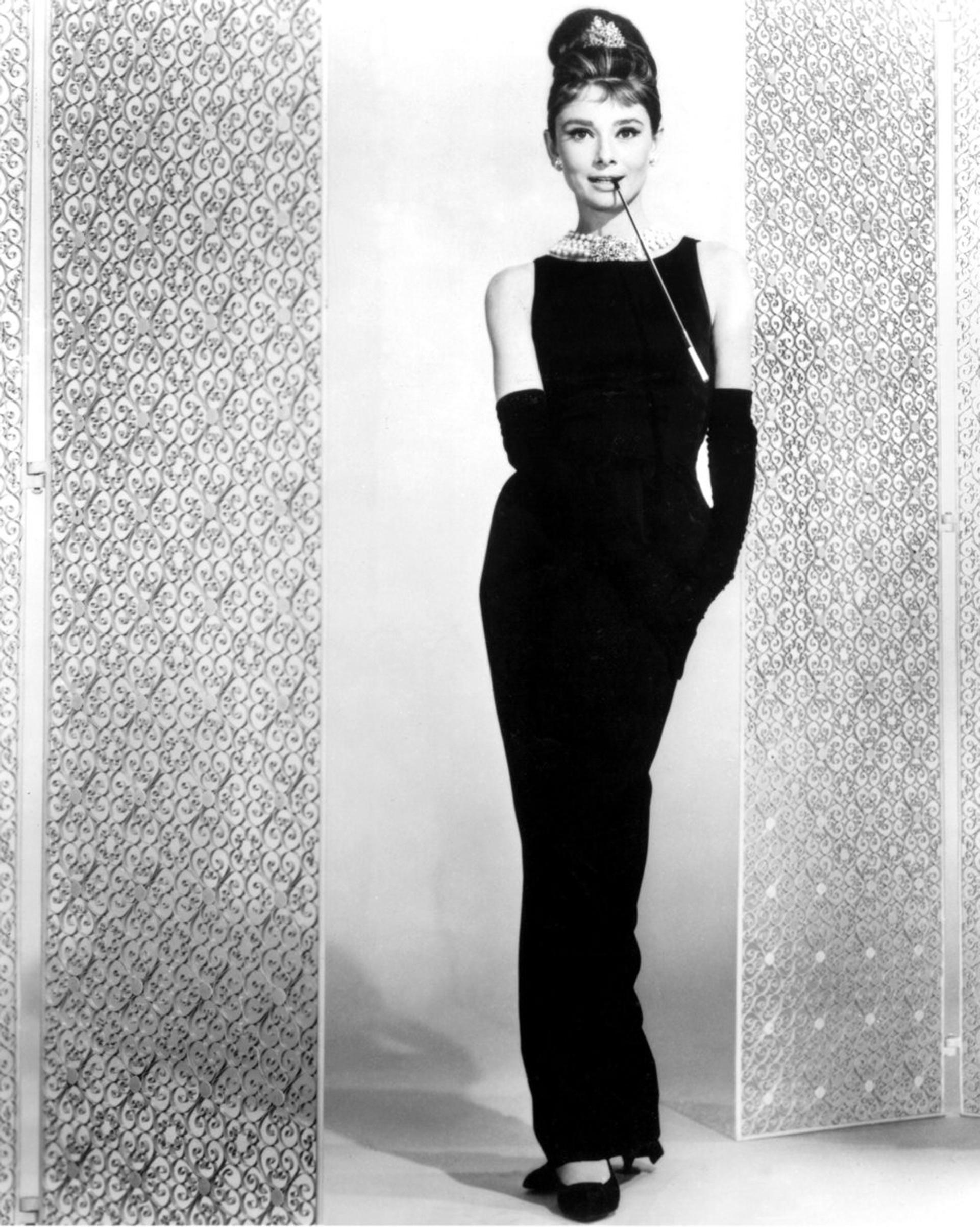 Audrey Hepburn en su película 'Breakfast at Tiffany's' lució un vestido sin mangas y guantes al codo en negro de Givenchy, diseñado exclusivamente para la actriz. A raíz de su película basada en su obsesión con la casa de joyas, lució una gargantilla de perlas y broche con brillantes