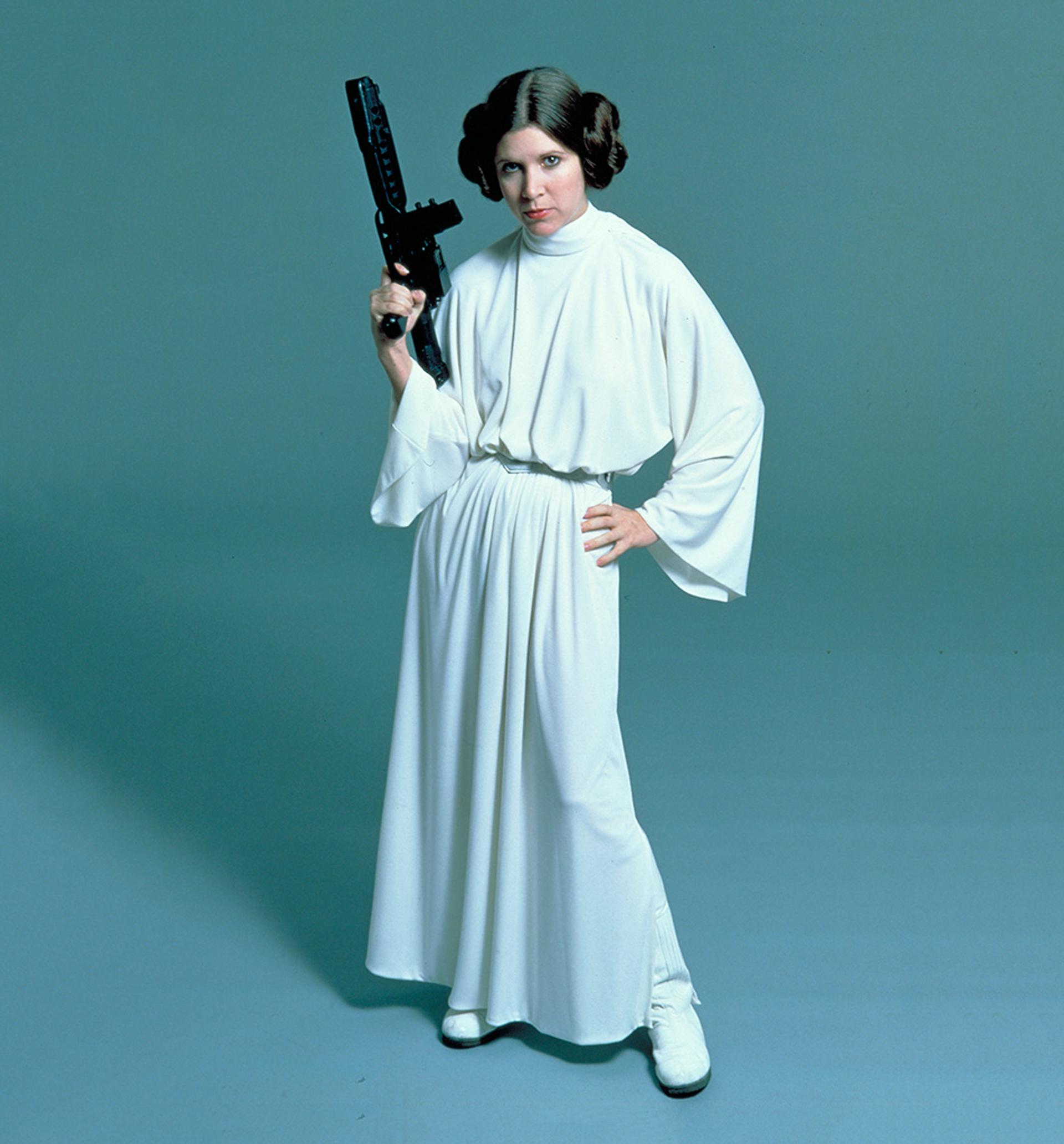 Carrie Fisher como Leia de Star Wars, con una túnica blanca con mangas acampanadas, cuello polera, faja en la cintura y botas blancas