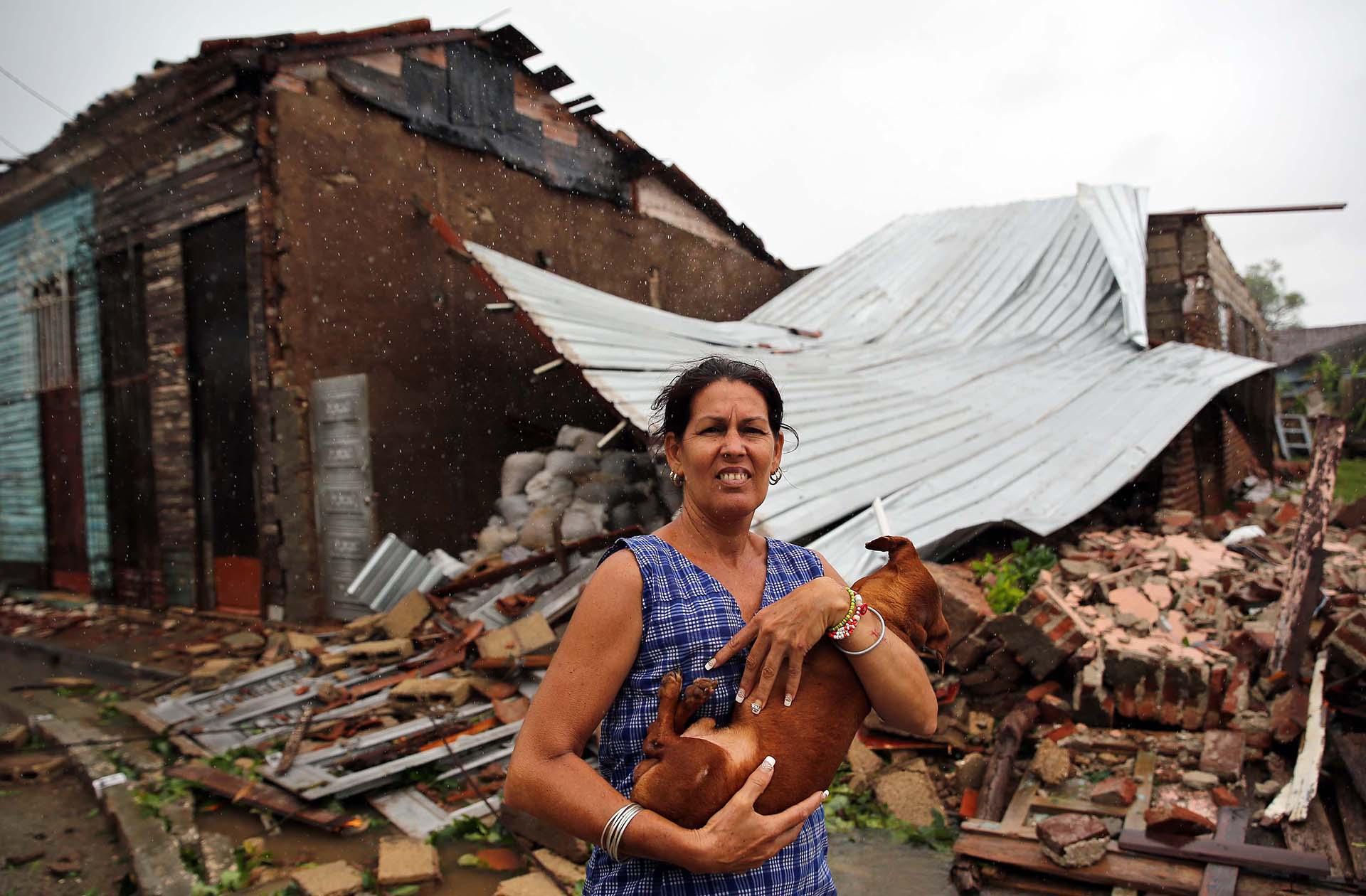 Una mujer posa con su perro frente a su casa destruida por el paso del huracán Irma en la ciudad central de Remedios, Cuba (EFE)