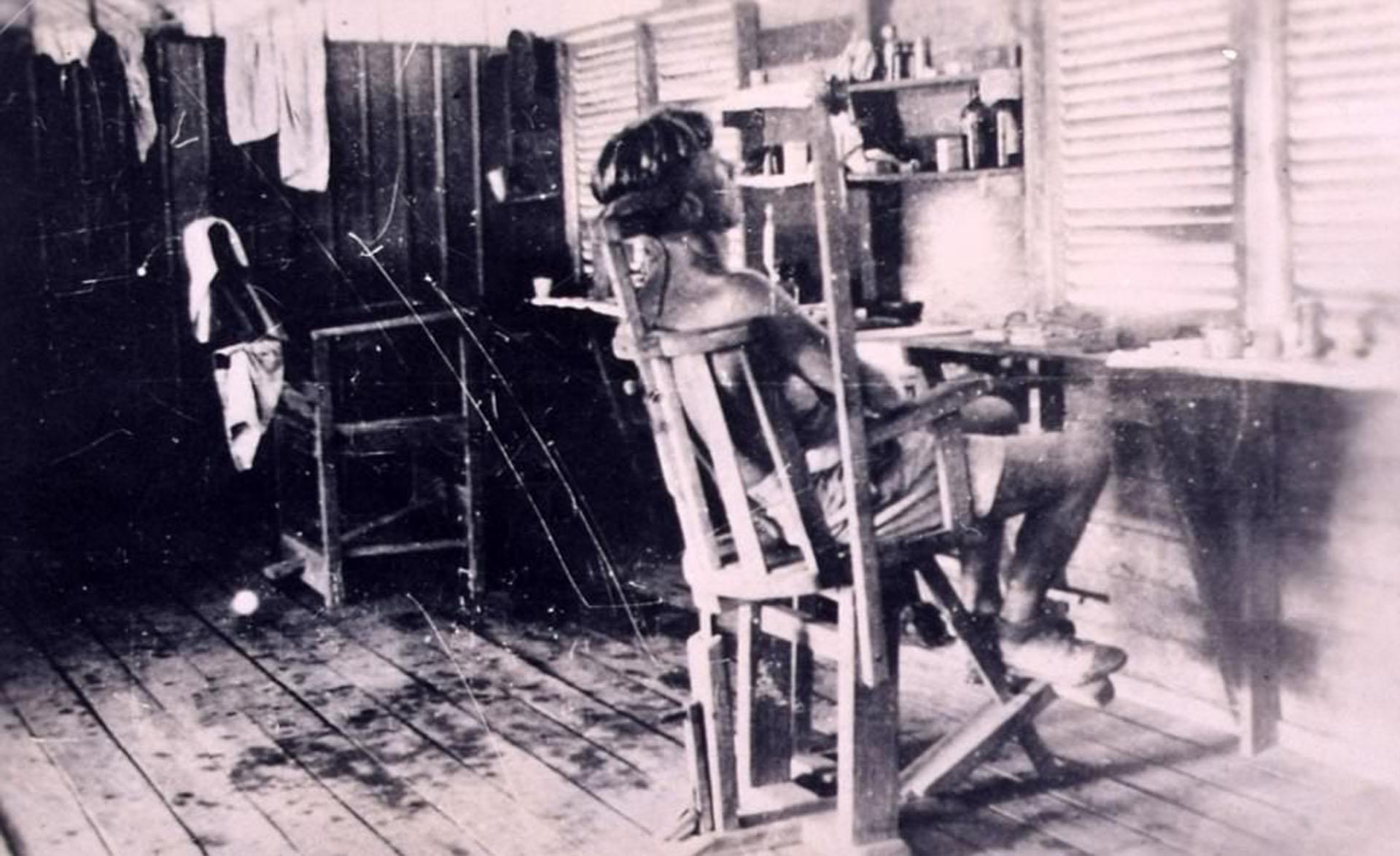 Un prisionero de guerrasentado en una silla de tortura en uno de los campos japoneses