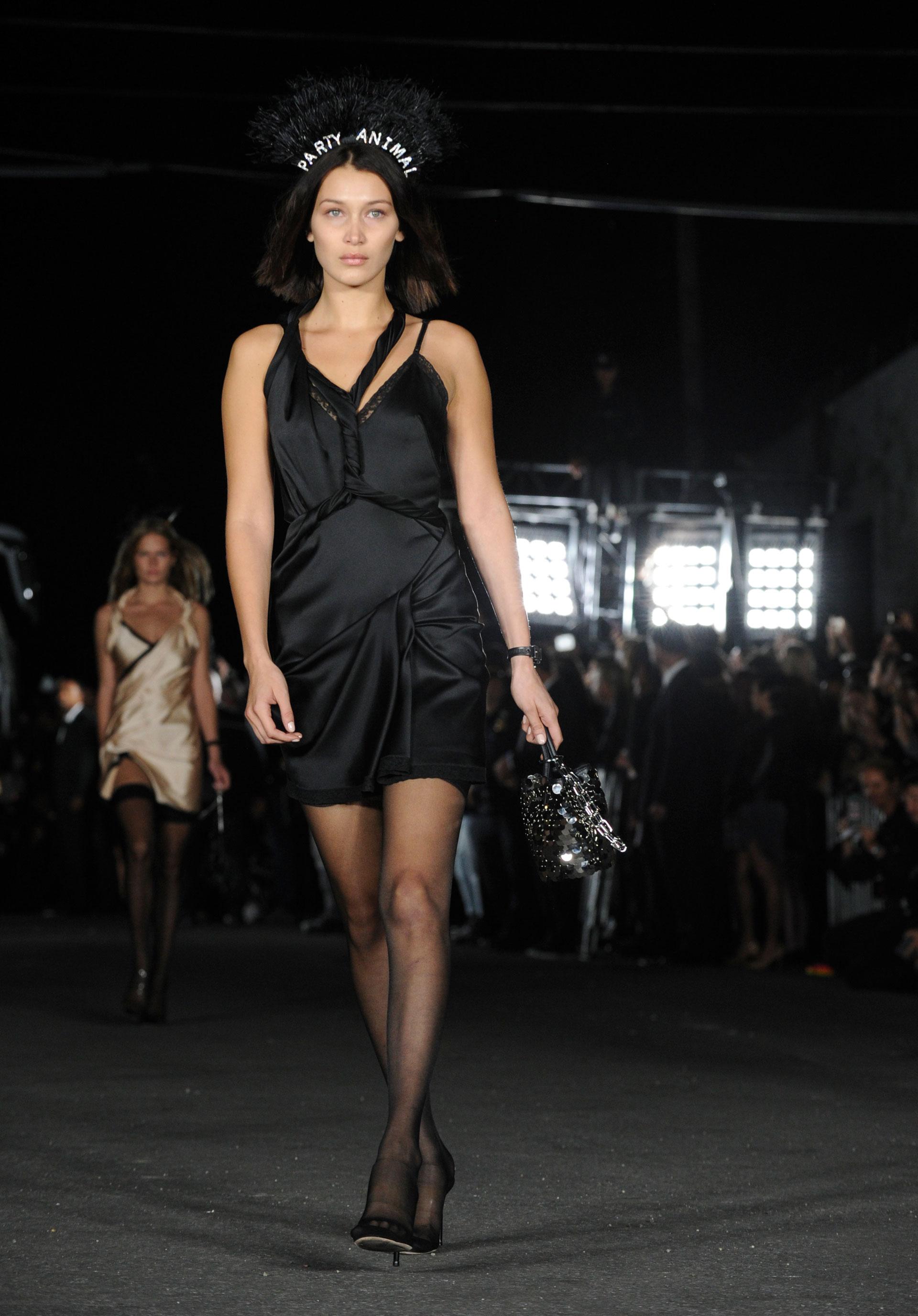 Vestidos lenceros de encaje y satén. Medias 7/8 y stilettos negros. En pasarela la top Bella Hadid con nuevo cambio de look (AP)