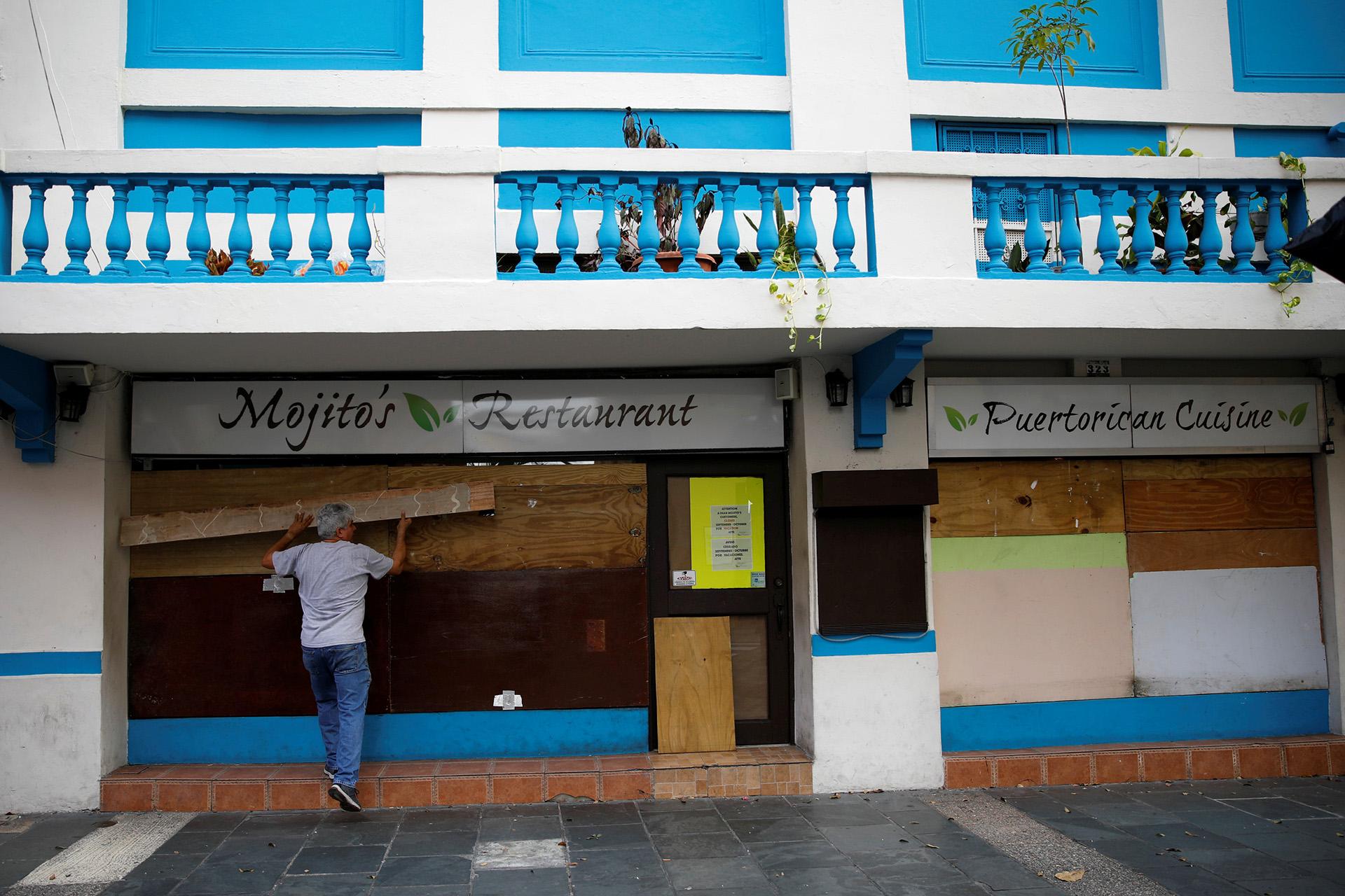 Vecinos en Puerto Rica protegieron los escaparates con tablones de madera ante la llegada de María