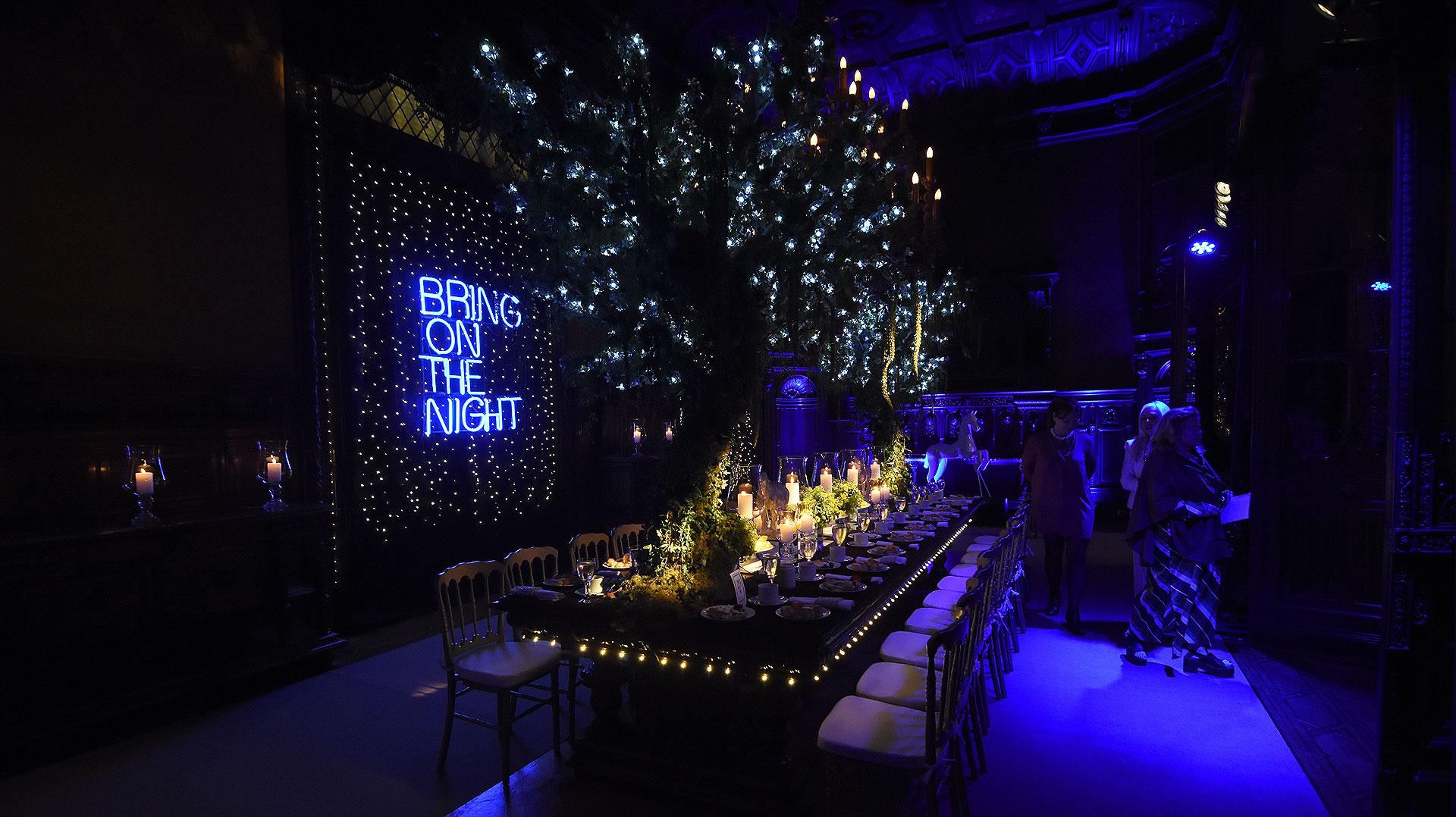 Un estilo boscoso, con luces LED alrededor de la mesa, fanales sobre cápsulas de vidrio y vajilla en blanco