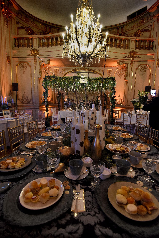 """""""Aura"""" por Pieres Michelson junto a botellas pintadas en blanco y dorado en el centro de la mesa, la vajilla elegida fueron colores monocromáticos, grises, blanco y negro"""