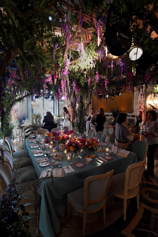 """""""Momentos con sentido"""" by Gloria Cesar. Una de las mesas principales entre árboles con flores en caída y centros de mesa con rosas, fresias en amarillo, violeta y rosas. Vajilla de colores y diseños sobre un mantel aguamarina"""