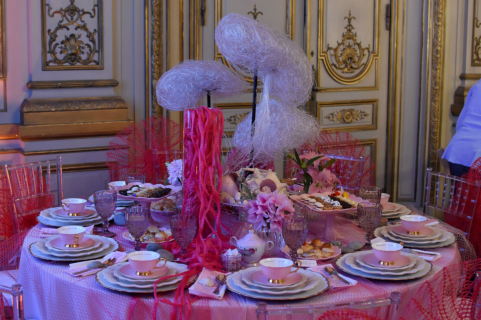 """""""Arrecife de Coral"""" por Pato Lotscher, todo en red rosa y blanco, vajilla rosada y flores a tono. Las sillas Tiffany elegidas eran de acrílico"""