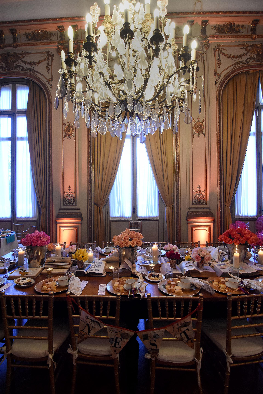"""""""Mil y una"""", por Nori Estrada. Centros de mesa primaverales con rosas fucsia, naranjas y degradé de rosa acompañado por libros abiertos. Sin mantel sobre la mesa de madera, platos del mismo material y las delicatessen propuestas para el té"""
