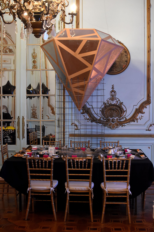 """""""Alma D Diamante"""". Una estructura de alambre sostiene al diamante dorado. Mantel y servilletas negras y grises. Detalles en fucsia y la elección de las sillas Tiffany"""