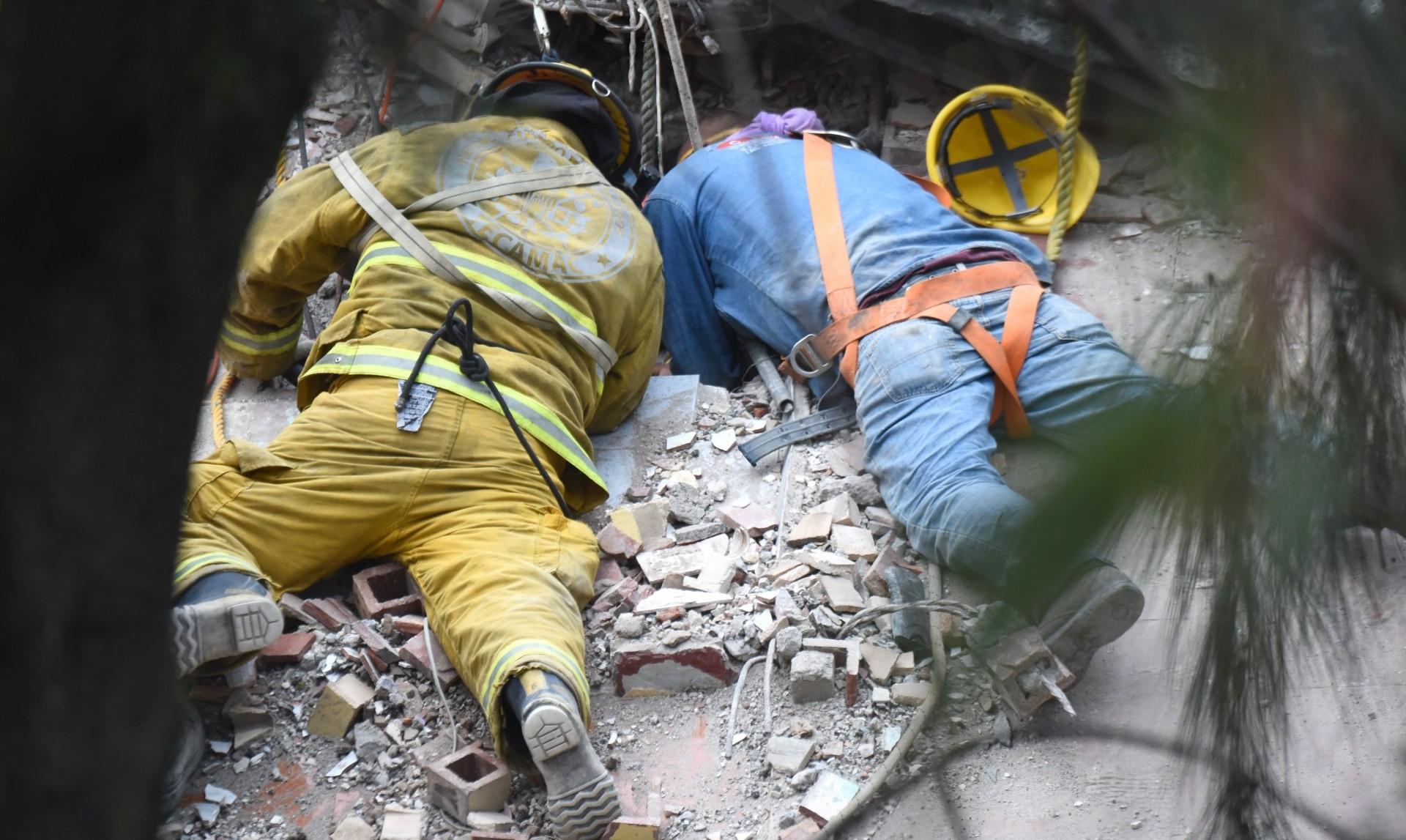 Un bombero y un rescatista excavan para llegar hasta las víctimas atrapadas en la Ciudad de México (AFP)