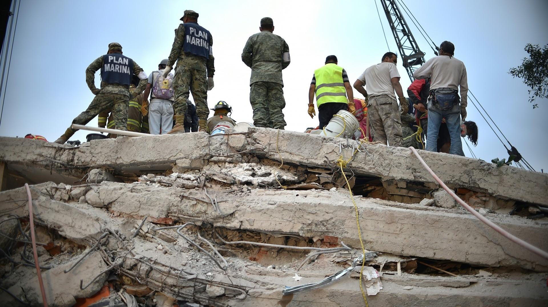Rescatistas, bomberos, policías y voluntarios buscan a sobrevivientes en un edificio de la capital (AFP)