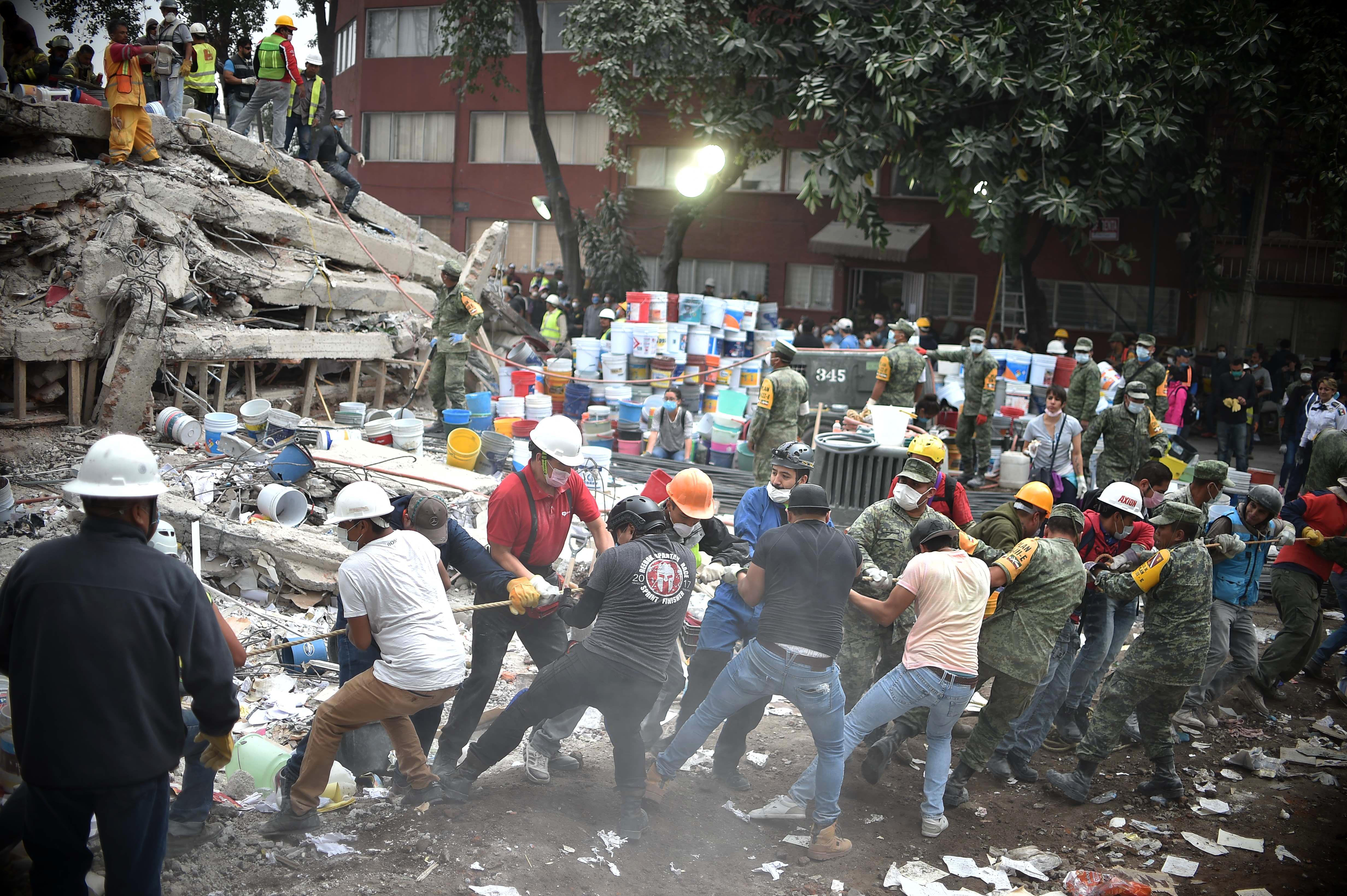Una cadena humana trabaja para remover los escombros de un edificio de la capital