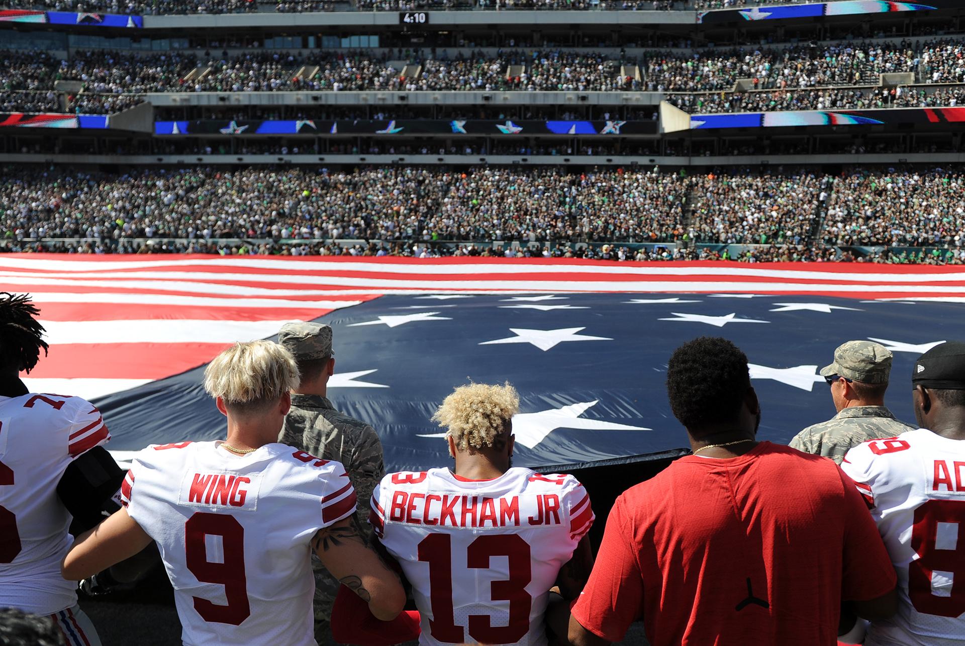 Odell Beckham Jr (13) cruzalos brazos con el puntero Brad Wing (9) durante el himno nacional antes del partido contra los Philadelphia Eagles en el Lincoln Financial Field