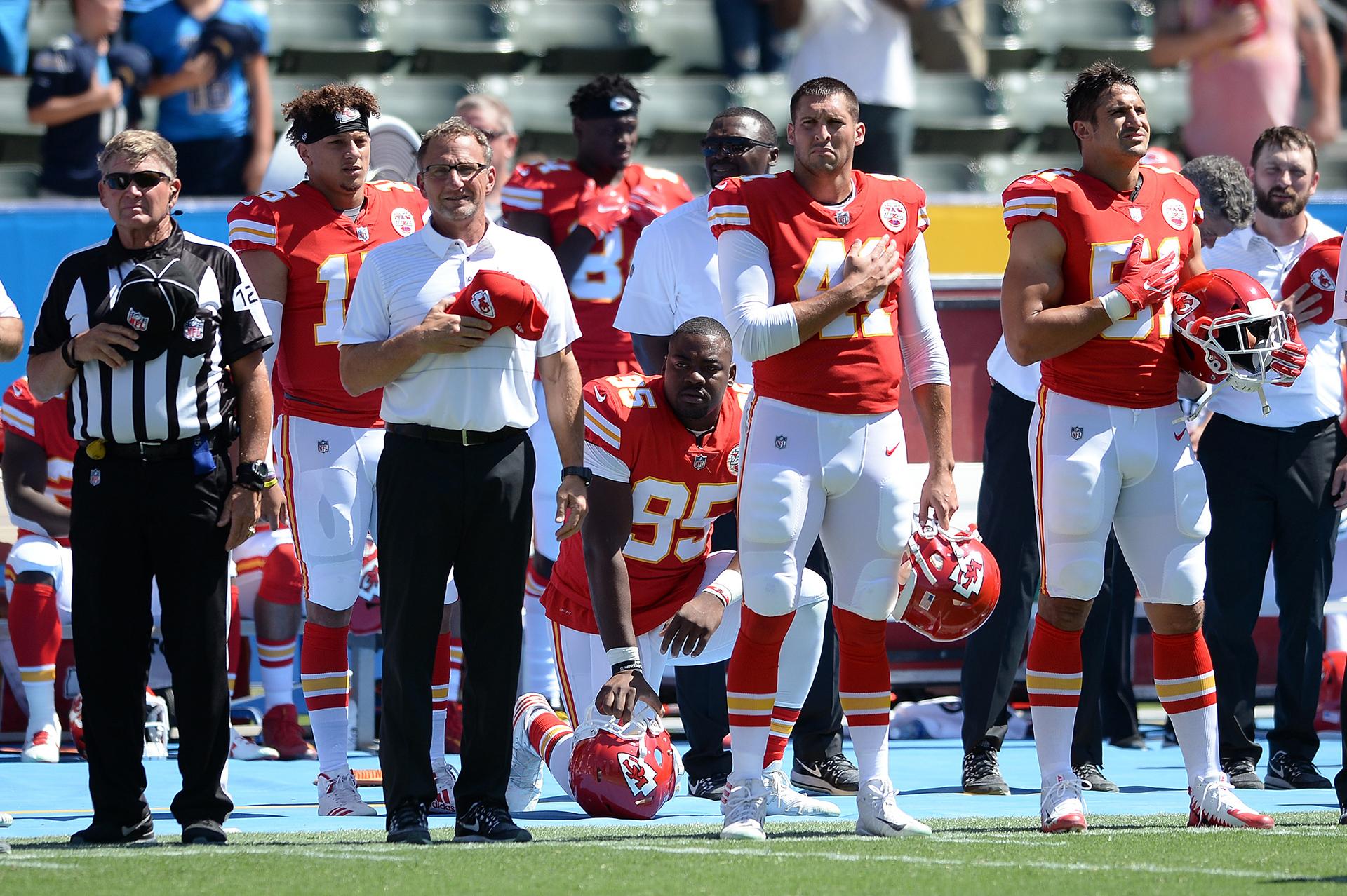 El extremo defensivo de Kansas City Chiefs Chris Jones (95) se arrodilla en protesta durante el himno nacional antes del partido contra los Chargers de Los Ángeles en el Centro StubHub.