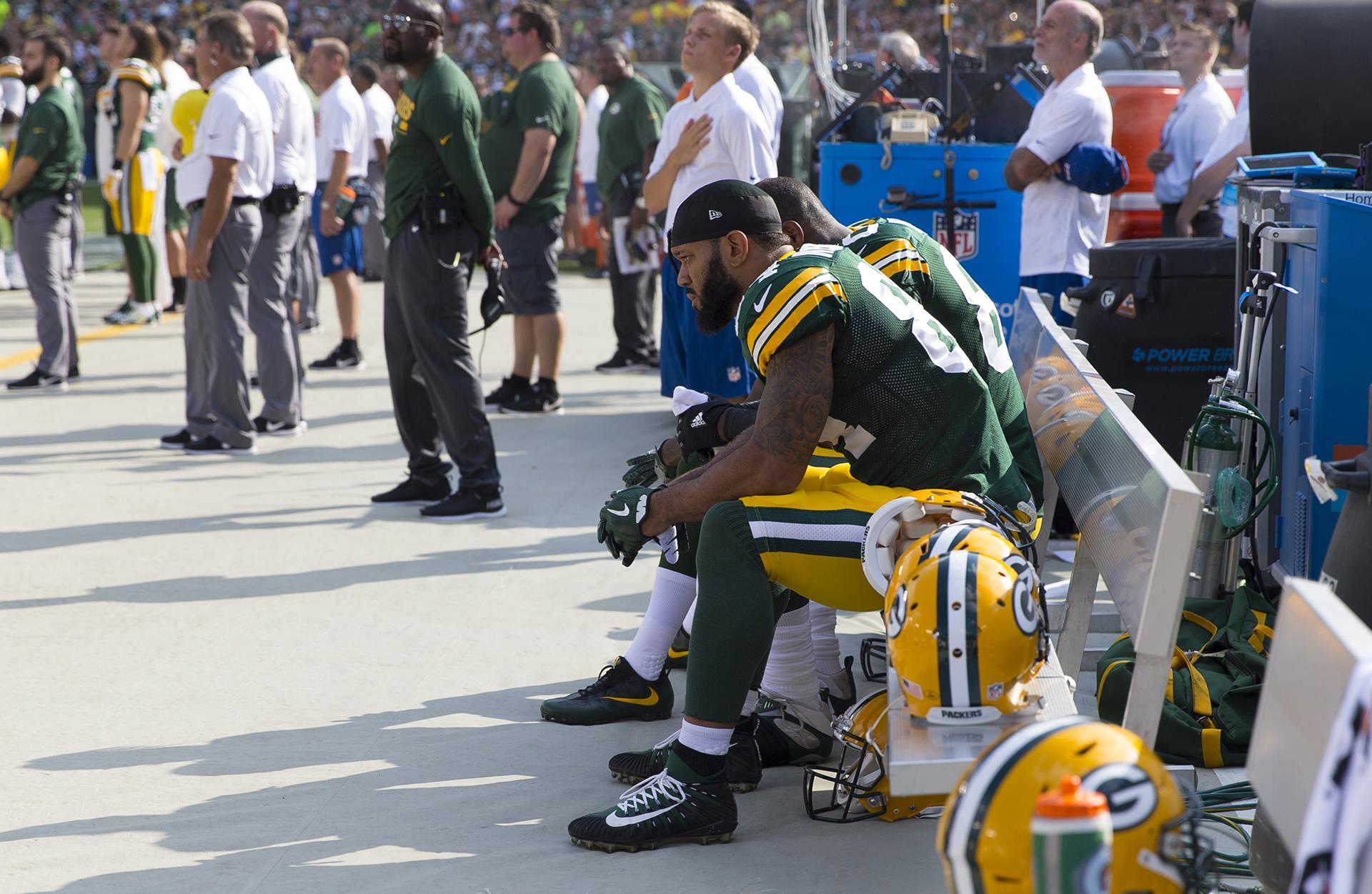 Green Bay Packers: Lance Kendricks (84) y Martellus Bennett (80) se sientan en el banco durante el himno nacional antes del juego contra los Cincinnati Bengals en el campo de Lambeau