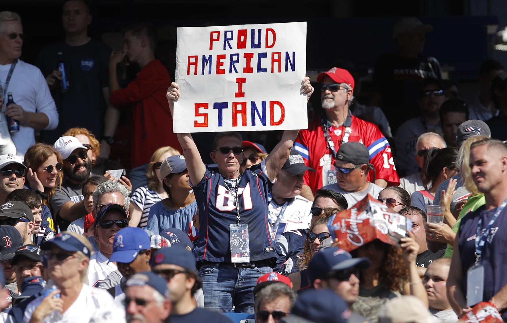 """Un fanáticode los patriots de Nueva Inglaterra lleva uncartel durante el enfrentamiento antelos Texans de Houston en la segunda mitad en el estadio de Gillette: """"orgullo americano, estoy de pie"""""""