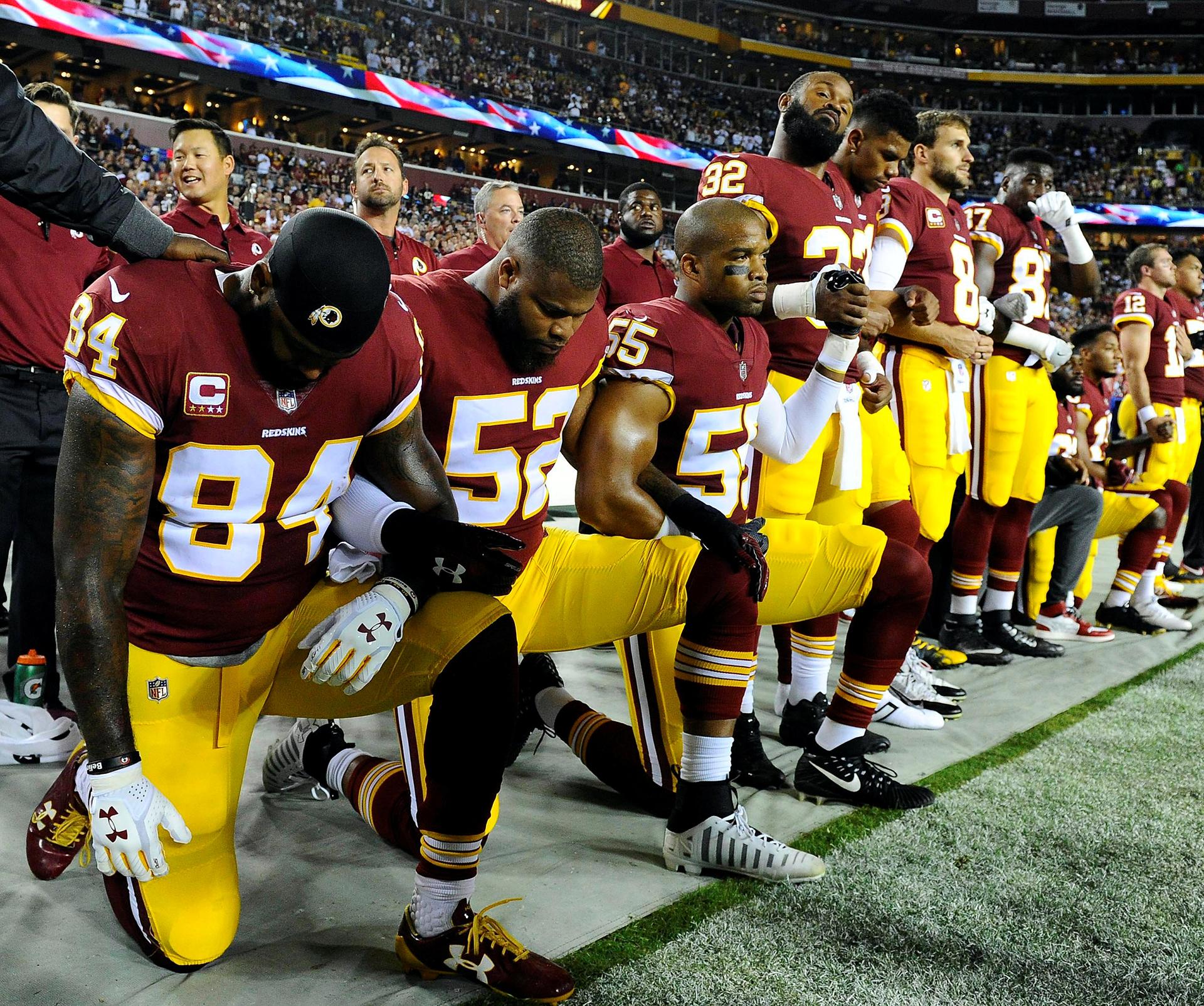 Niles Paul (84) y el apoyador de Washington Redskins Chris Carter (55) se arrodillan con sus compañeros de equipo durante el himno nacional antes del partido entre los Redskins de Washington y los Raiders de Oakland