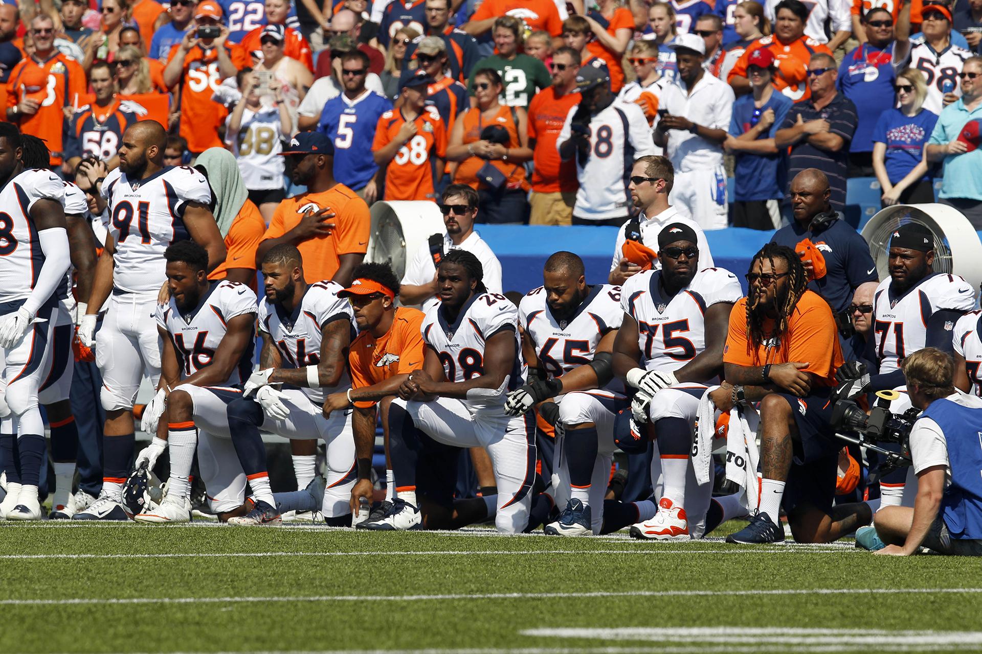 Los jugadores de Denver Bronco se arrodillan en protesta durante el Himno Nacional antes de un partido contra los Buffalo Bills