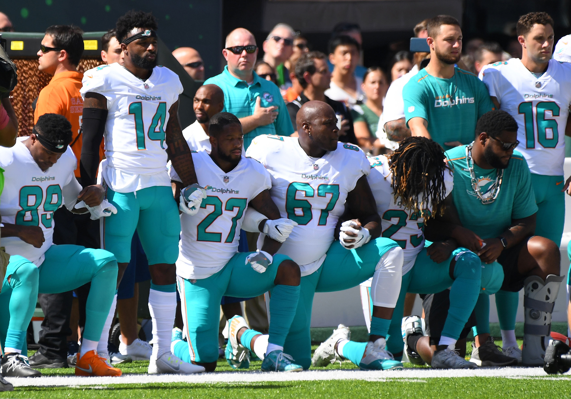 Algunos de los Miami Dolphinsse posan sobreuna rodilla durante el himno antes del juego contra los jets de Nueva York en el estadio de MetLife.