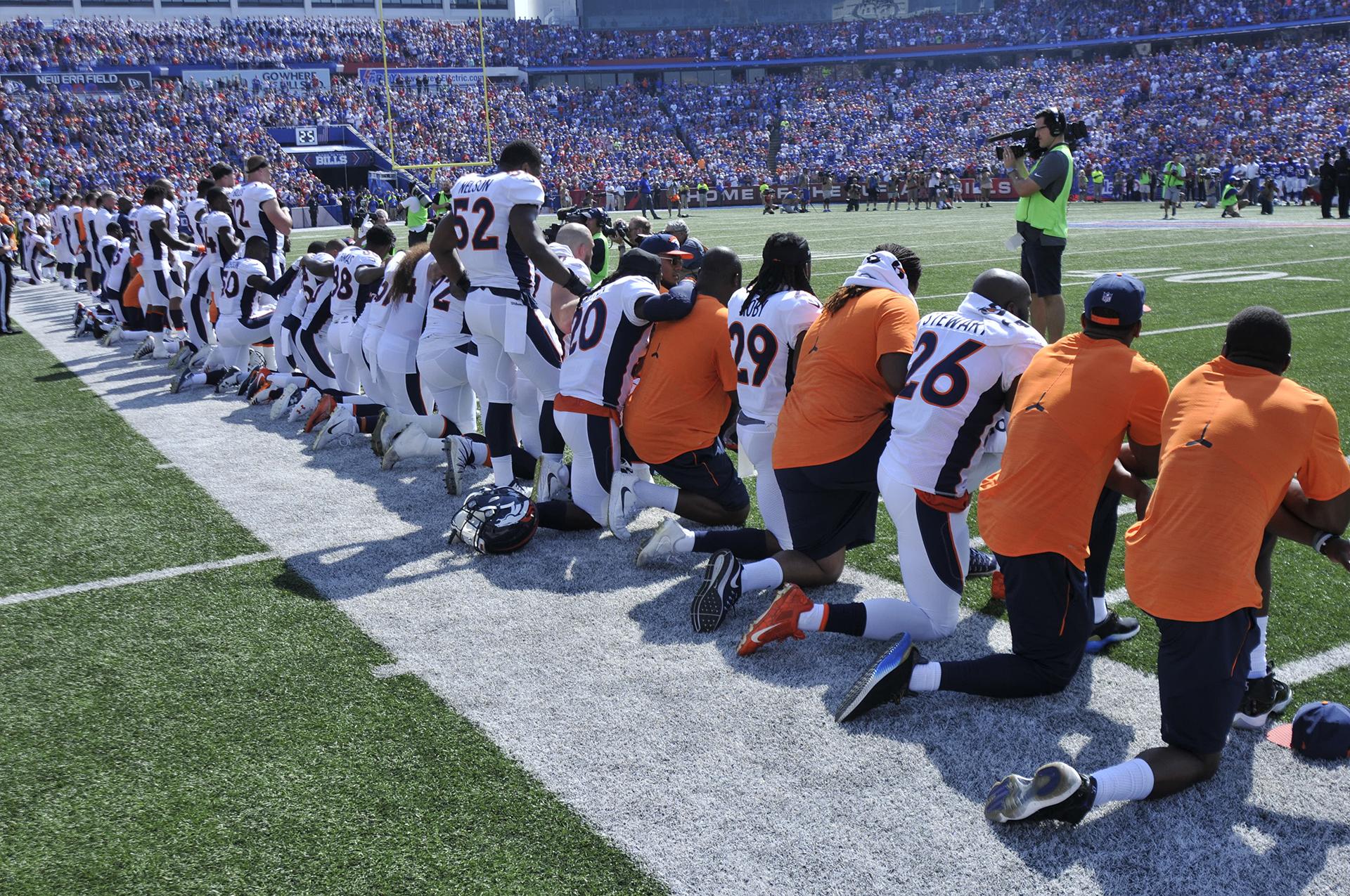 Los miembros de los Denver Broncos se arrodillan durante el juego del himno nacional antes de un partido contra los Buffalo Bills