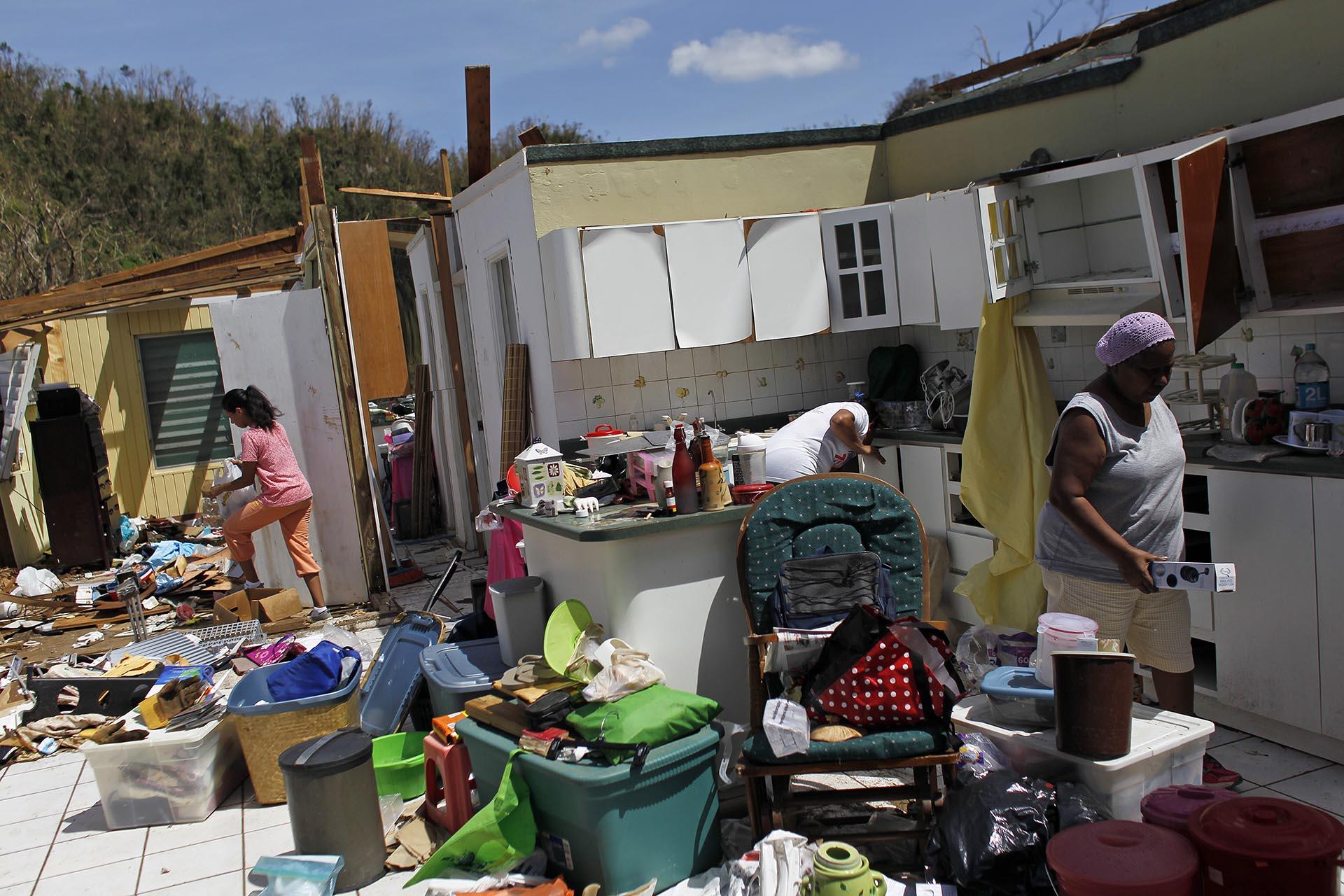 Una familia recoge sus cosas luego de que el huracán le arrancara el techo a su casa enToa Baja, en el oeste de San Juan, Puerto Rico