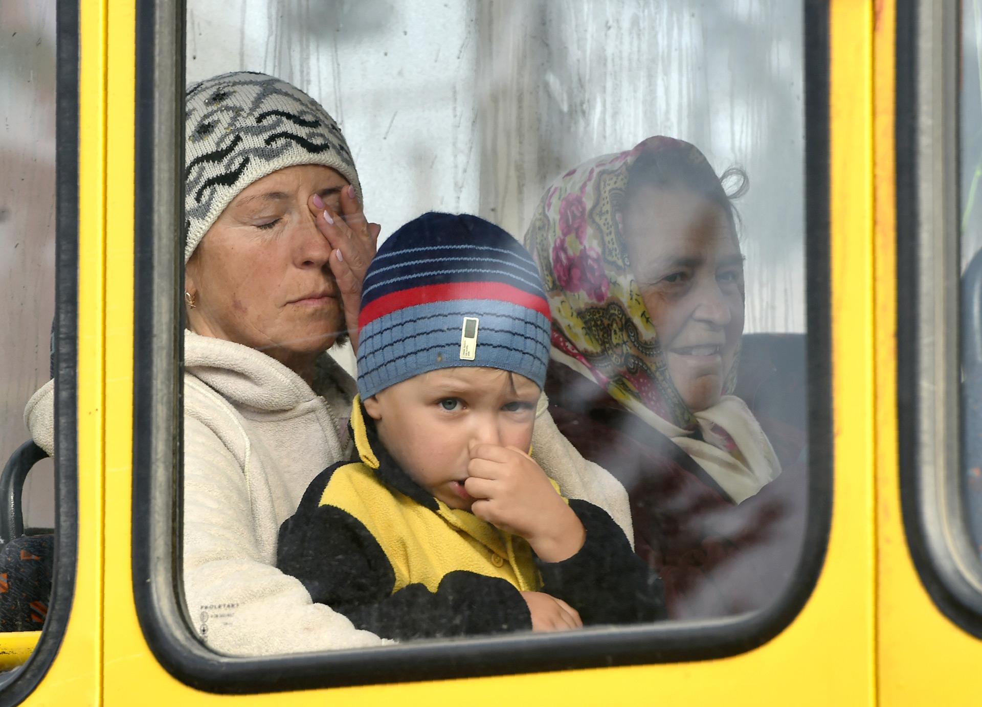 Una familia al momento de ser evacuada por las autoridades (AFP)