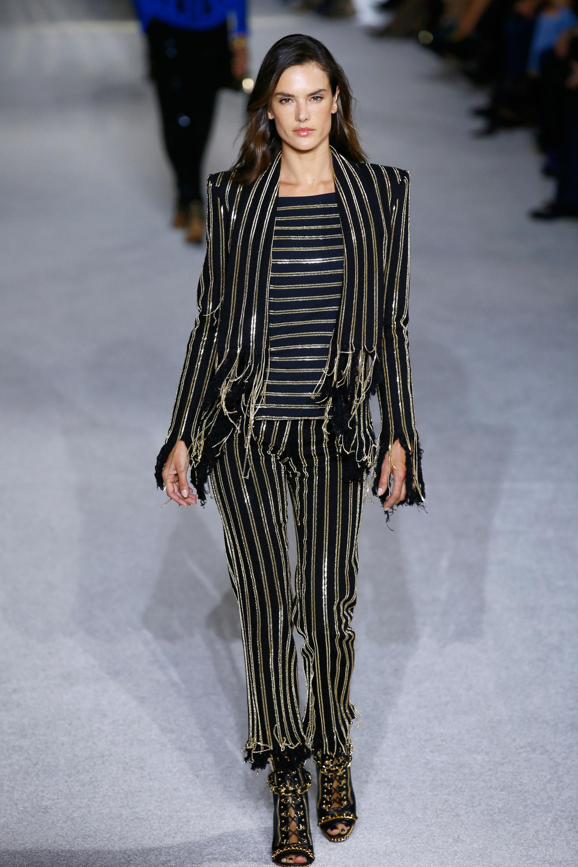 Alessandra Ambrosio, la top model de Victoria's Secret, subió a la pasarela de Balmain. Rayas verticales y horizontales de cadenas doradas sobre pantalón, camisa y blazer fue su pasada