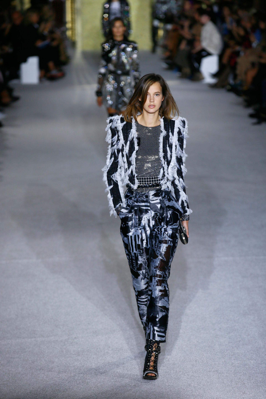 Chaquetas con hombreras combinadas con plumas blancas, pantalones en taftan con diseño abstracto y booties en charol negro con tientos