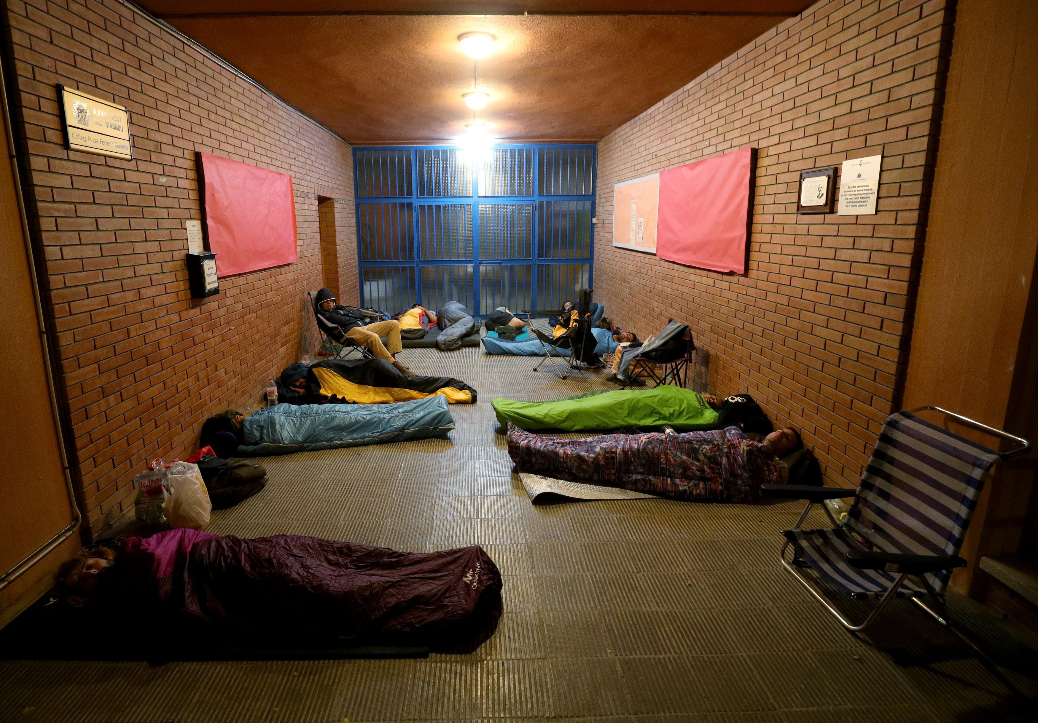 Un grupo de personas duerme dentro de un colegio tomado donde se realizaran votaciones. (REUTERS/Albert Gea)